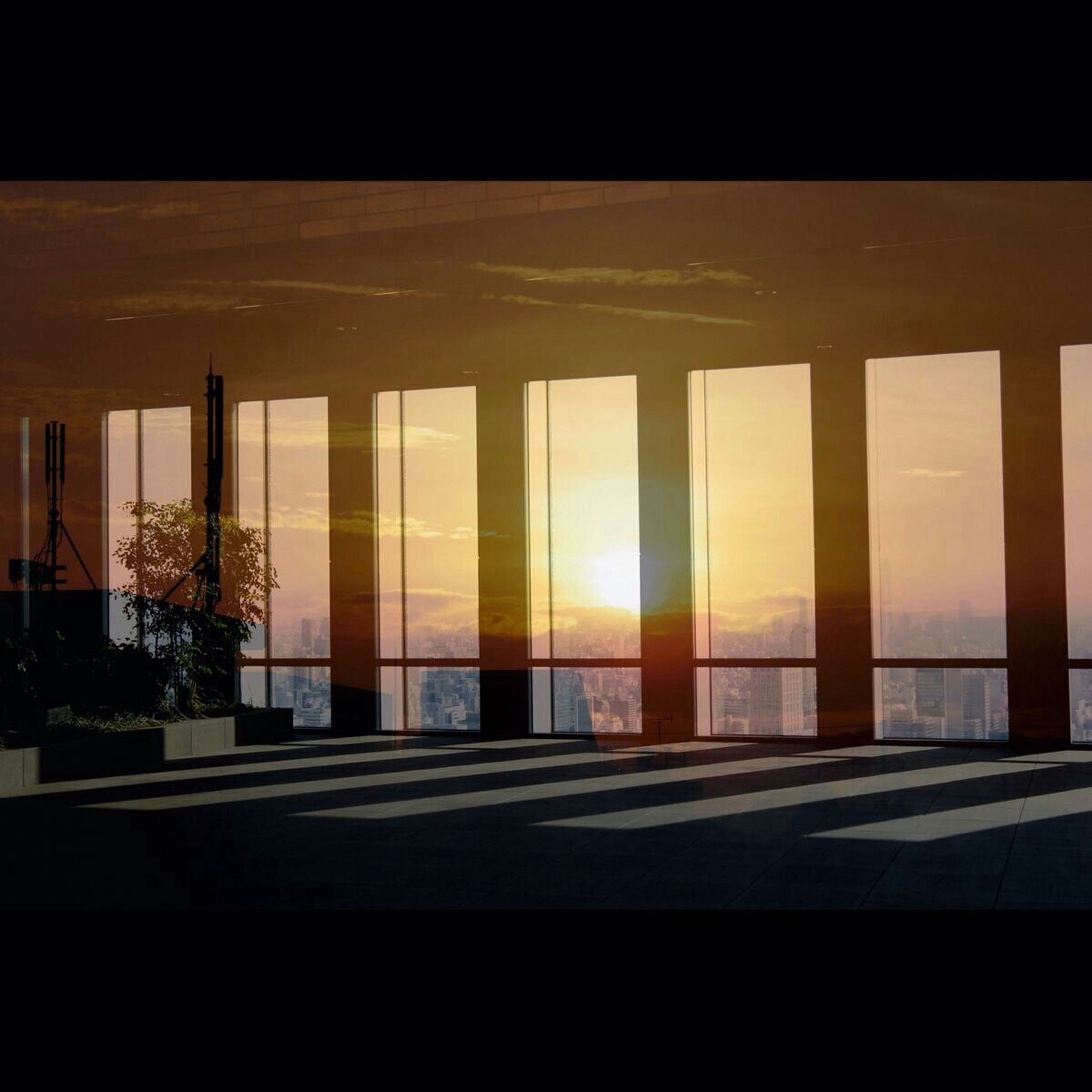 architecture, built structure, sunlight, building exterior, sunset, indoors, window, sky, architectural column, glass - material, sun, sea, no people, building, silhouette, shadow, water, day, wood - material