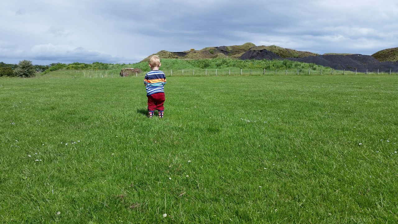 Boy Standing Field Grassy Green Hills Hill Outside The Great Outdoors With Adobe 2-3 Years Horizontal Children One Child Male Caucasian Coal Fence Blonde Rear View Grass And Sky Clouds And Sky Wellington Boots Trees Industrial Landscapes Non-urban Scene