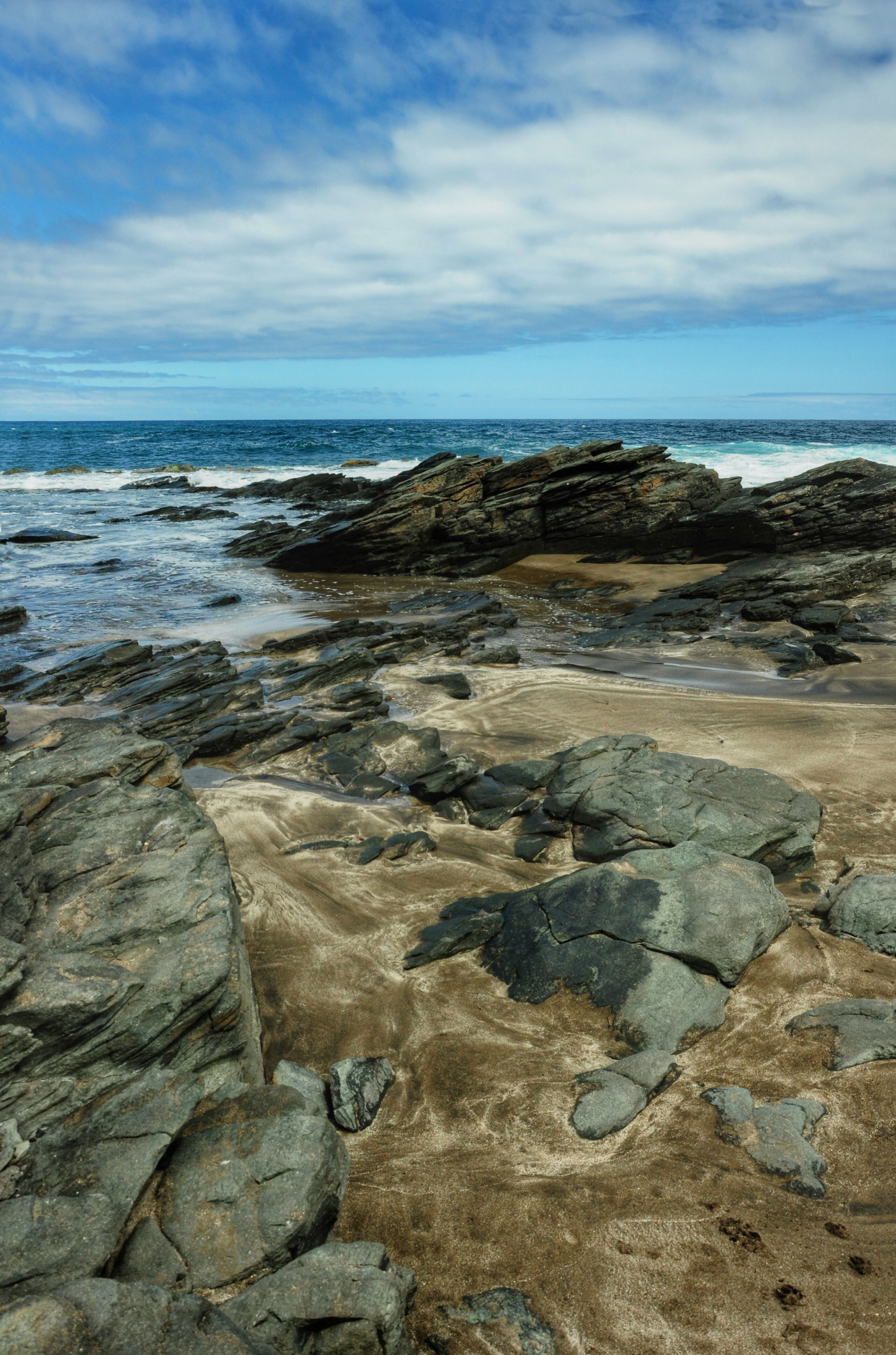 sea, sky, water, horizon over water, scenics, cloud - sky, tranquility, tranquil scene, rock - object, beauty in nature, beach, nature, shore, rock formation, cloud, cloudy, rock, idyllic, day, outdoors