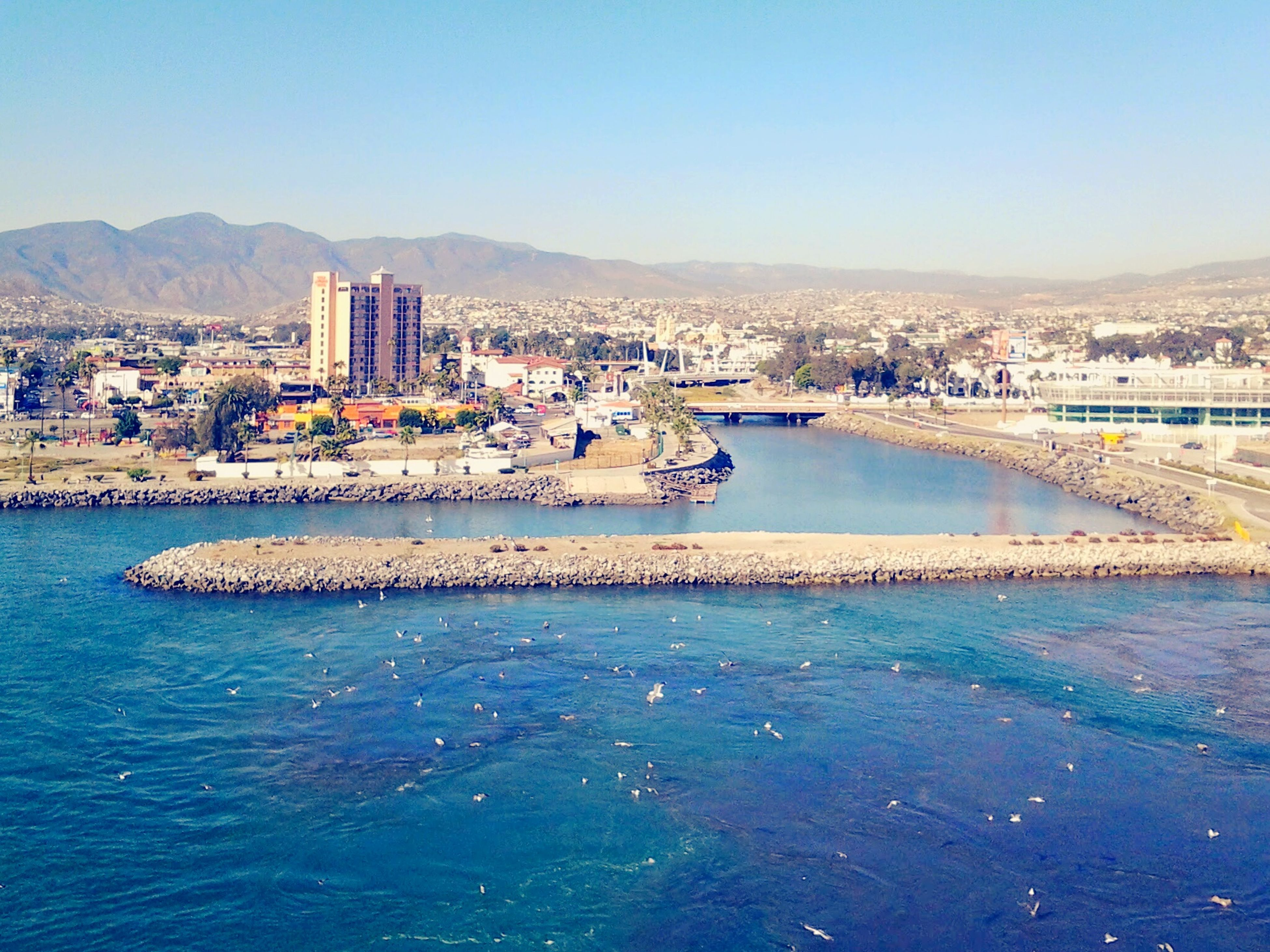 clear sky, water, built structure, architecture, copy space, building exterior, mountain, sea, blue, city, cityscape, river, coastline, beach, transportation, waterfront, mountain range, connection, outdoors, scenics