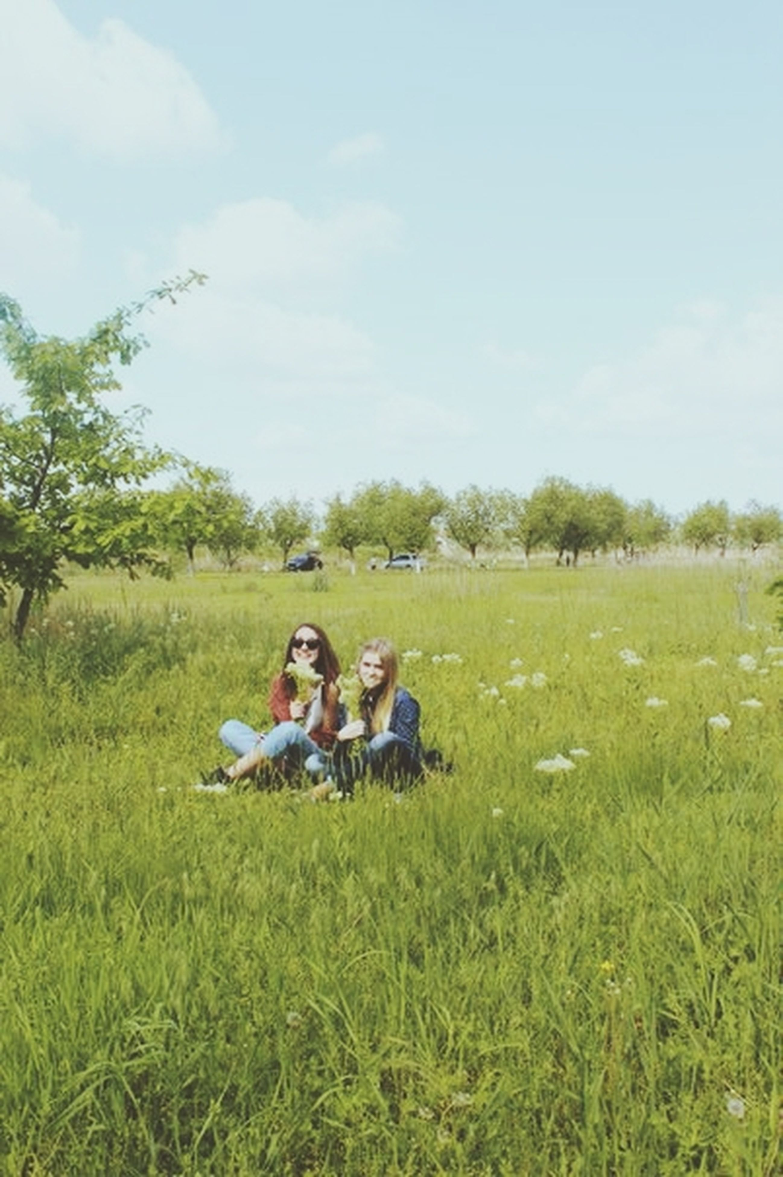 grass, lifestyles, leisure activity, sitting, field, full length, sky, casual clothing, men, relaxation, grassy, togetherness, green color, landscape, person, childhood, bonding
