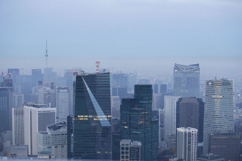 Tokyo skyscrapers seen from the Tokyo CityView in Roppongi, Tokyo Architecture Building Exterior Built Structure City Cityscape Day Downtown District Fog Japan Modern No People Outdoors Sky Skyscraper Tokyo Tower Travel Destinations Urban Skyline