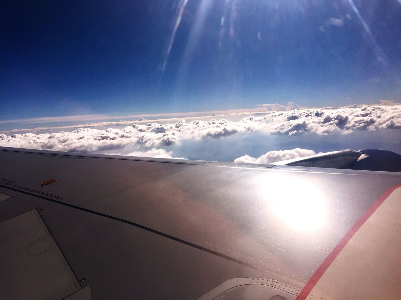airplane, beauty in nature, aerial view, transportation, sky, nature, air vehicle, no people, journey, scenics, airplane wing, aircraft wing, sunlight, cloud - sky, flying, tranquility, day, travel, tranquil scene, mode of transport, outdoors, blue, vehicle part