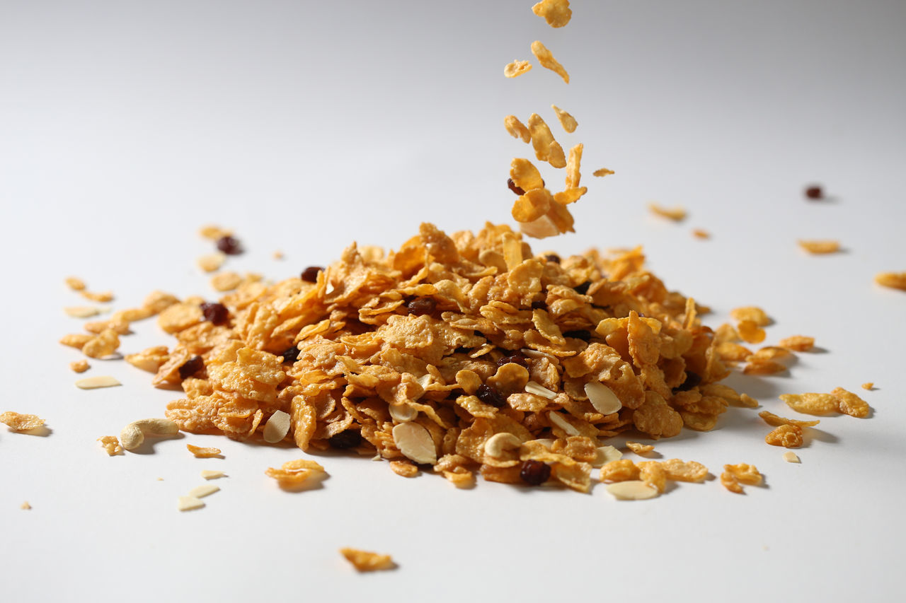Corn Flakes Falling Against White Background