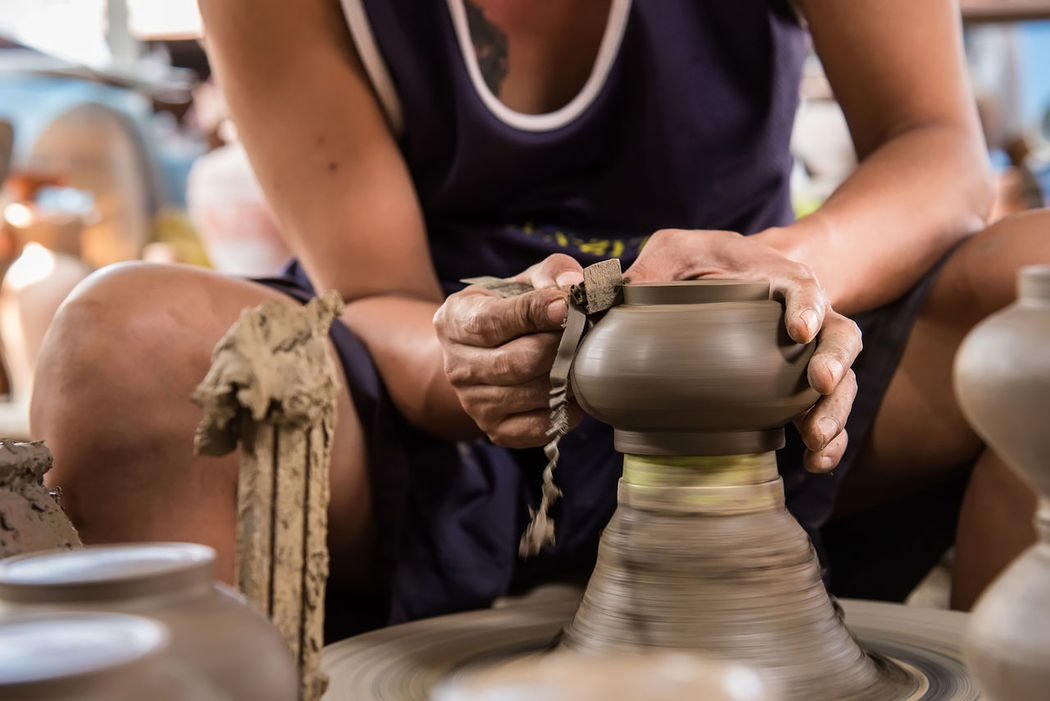 Nonthaburi, Thailand - February, 22, 2017 : Hand of potter man traditional pottery making shaping a bowl on the spinning by clay at Koh Kret Nonthaburi, Thailand. Adult Adults Only Art And Craft Artist Clay Craft Craftsperson Creativity Day Human Hand Indoors  Making Molding A Shape Mud One Person One Woman Only People Pottery Sculpture