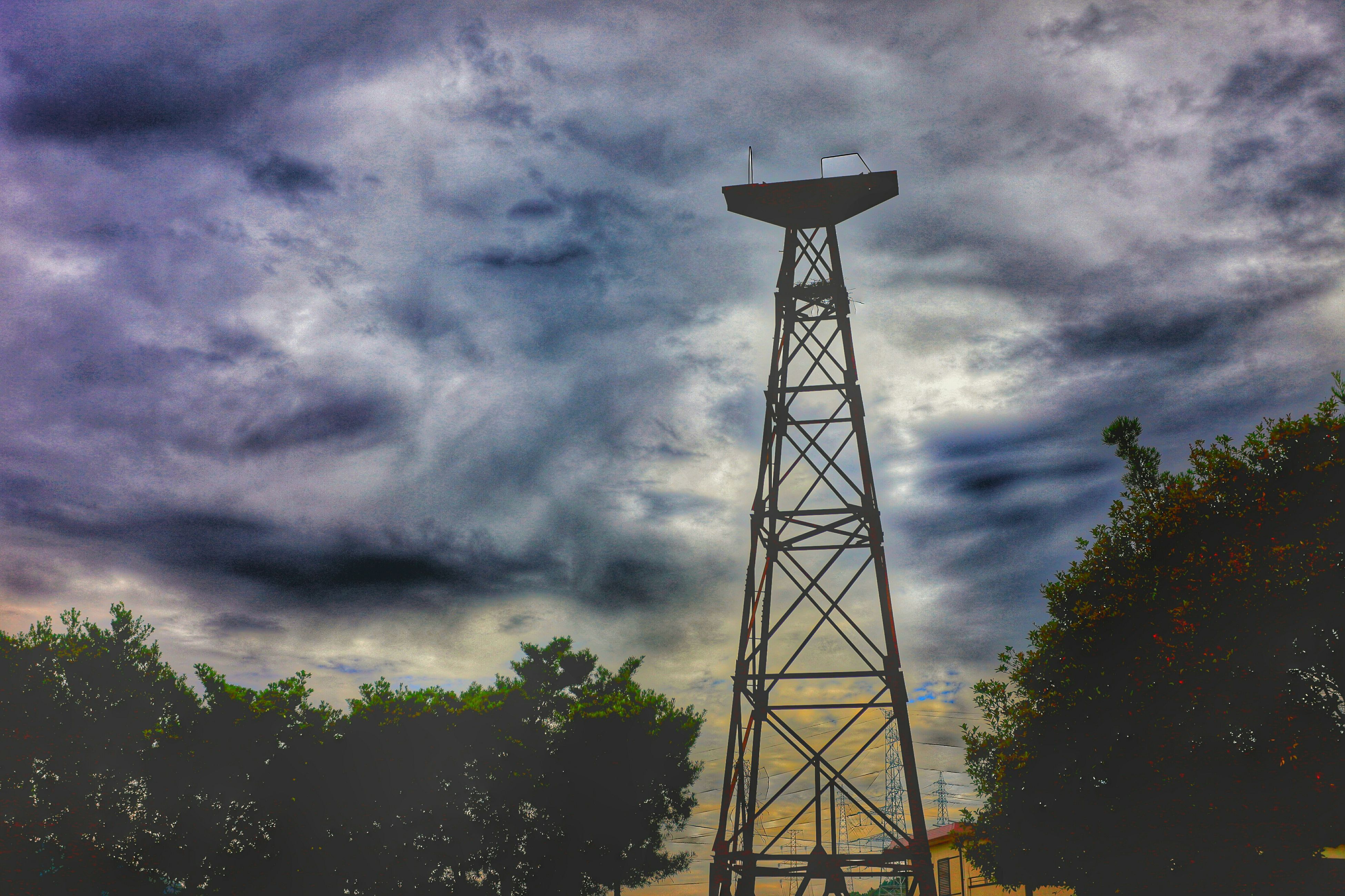 low angle view, sky, cloud - sky, cloudy, tree, silhouette, overcast, weather, connection, cloud, dusk, electricity pylon, tall - high, built structure, technology, electricity, nature, fuel and power generation, outdoors, metal