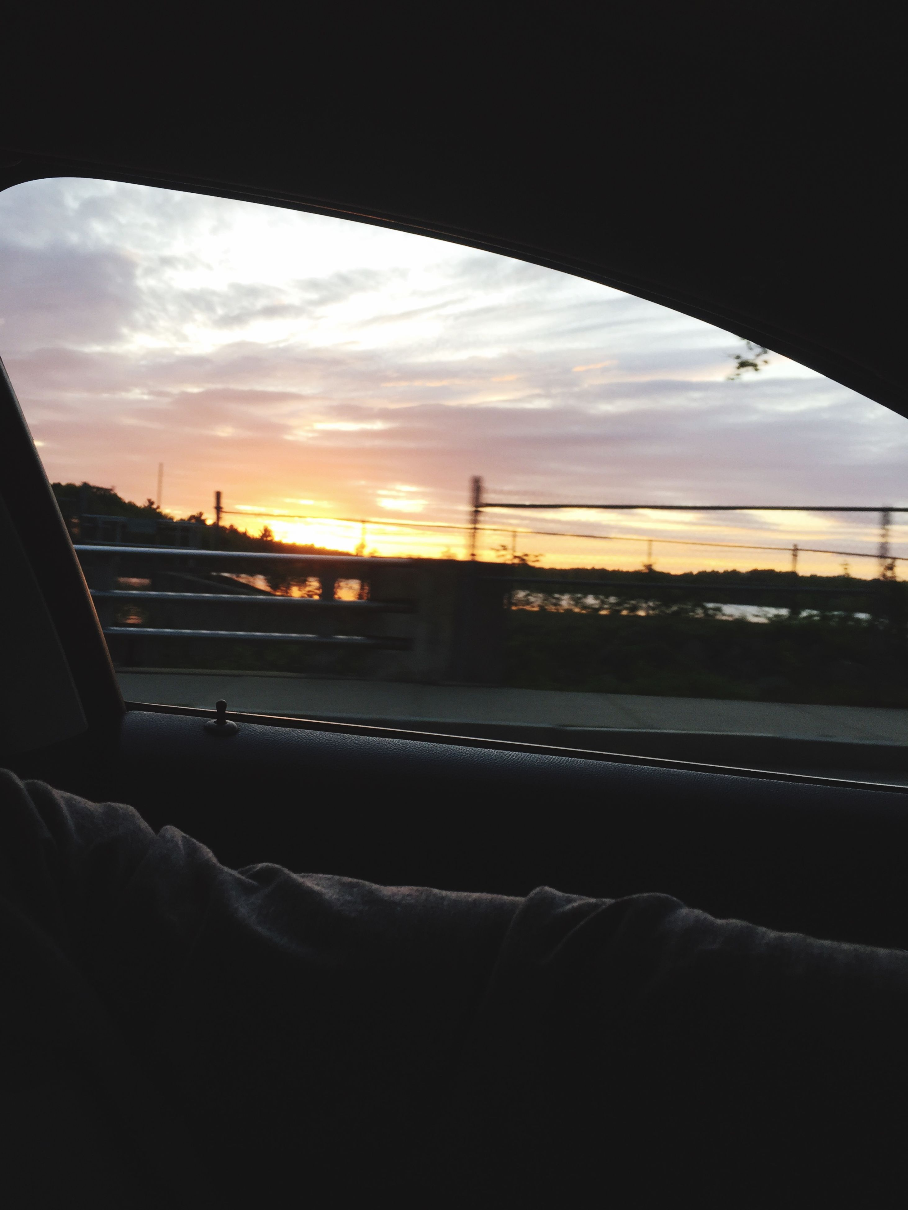 sunset, sky, transportation, cloud - sky, indoors, silhouette, mode of transport, built structure, window, architecture, cloud, vehicle interior, car, orange color, glass - material, land vehicle, transparent, reflection, travel, no people