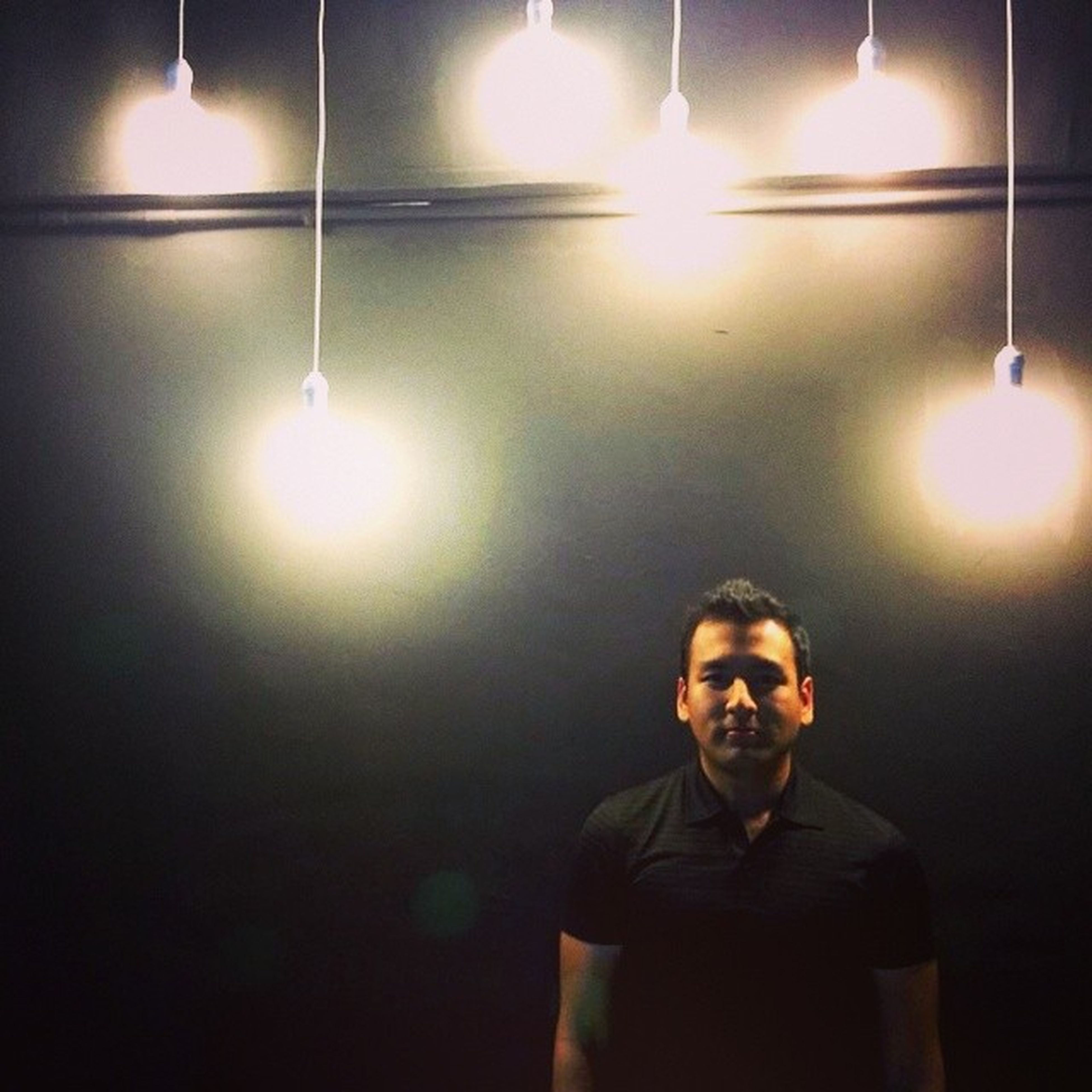 illuminated, indoors, lighting equipment, lifestyles, glowing, sun, lens flare, standing, leisure activity, sunbeam, candle, light - natural phenomenon, night, front view, men, electric light, wall - building feature, lit