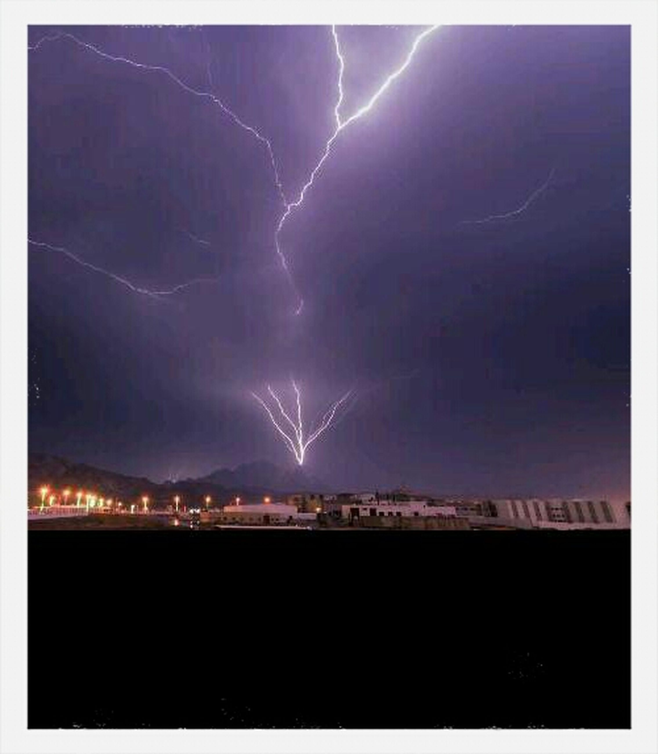 night, illuminated, sky, scenics, power in nature, mountain, beauty in nature, lightning, thunderstorm, built structure, dark, nature, electricity, light, building exterior, cityscape, city, architecture, light - natural phenomenon, glowing