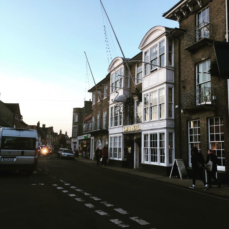 Architecture Building Building Exterior Built Structure Car City City Life City Street Clear Sky Incidental People Men Mode Of Transport Road Sky Southwold Street Street Light Swan Hotel Walking