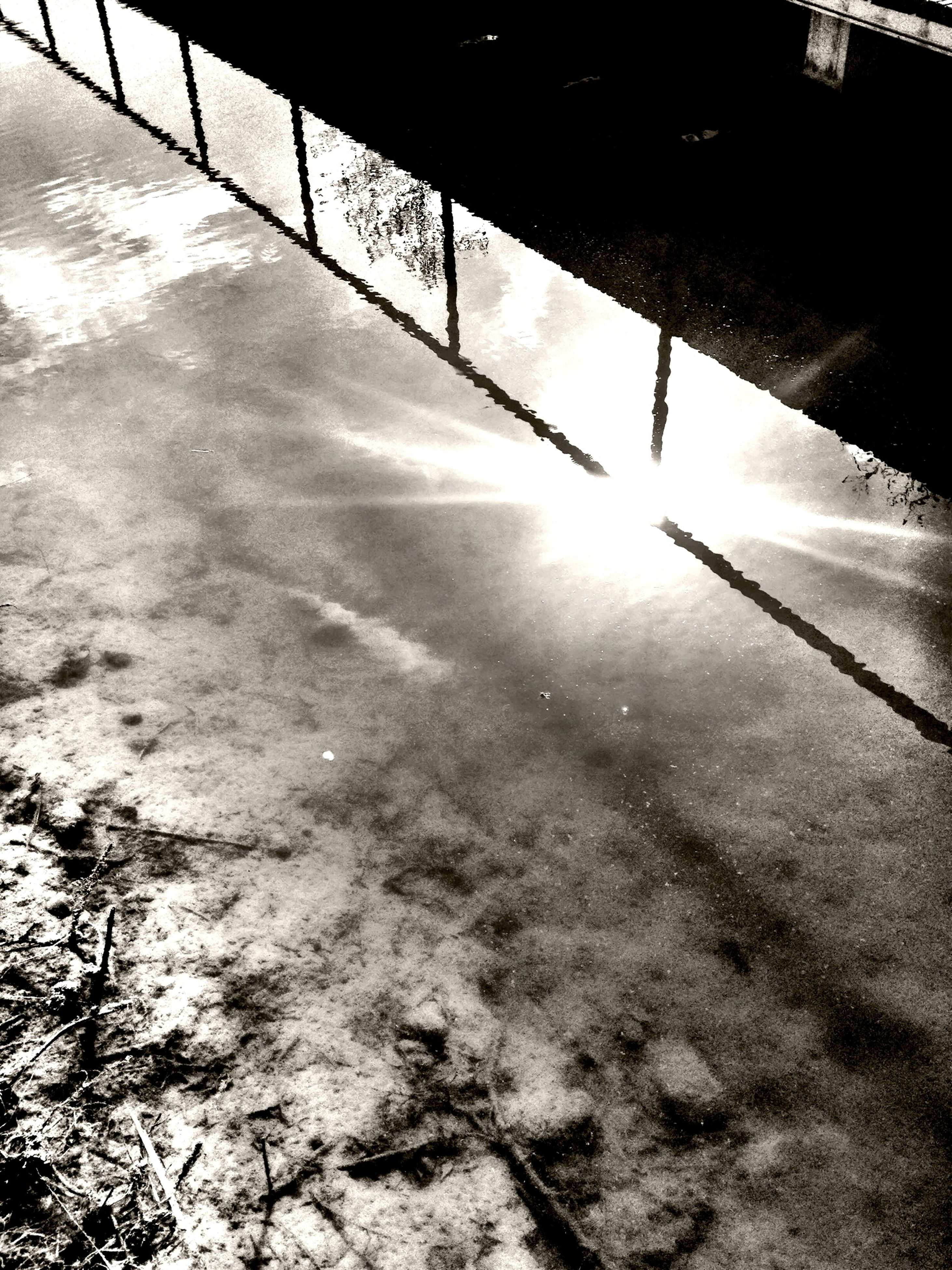 water, reflection, puddle, high angle view, wet, street, shadow, sunlight, rain, outdoors, season, road, built structure, day, nature, city, sidewalk, river, weather, no people