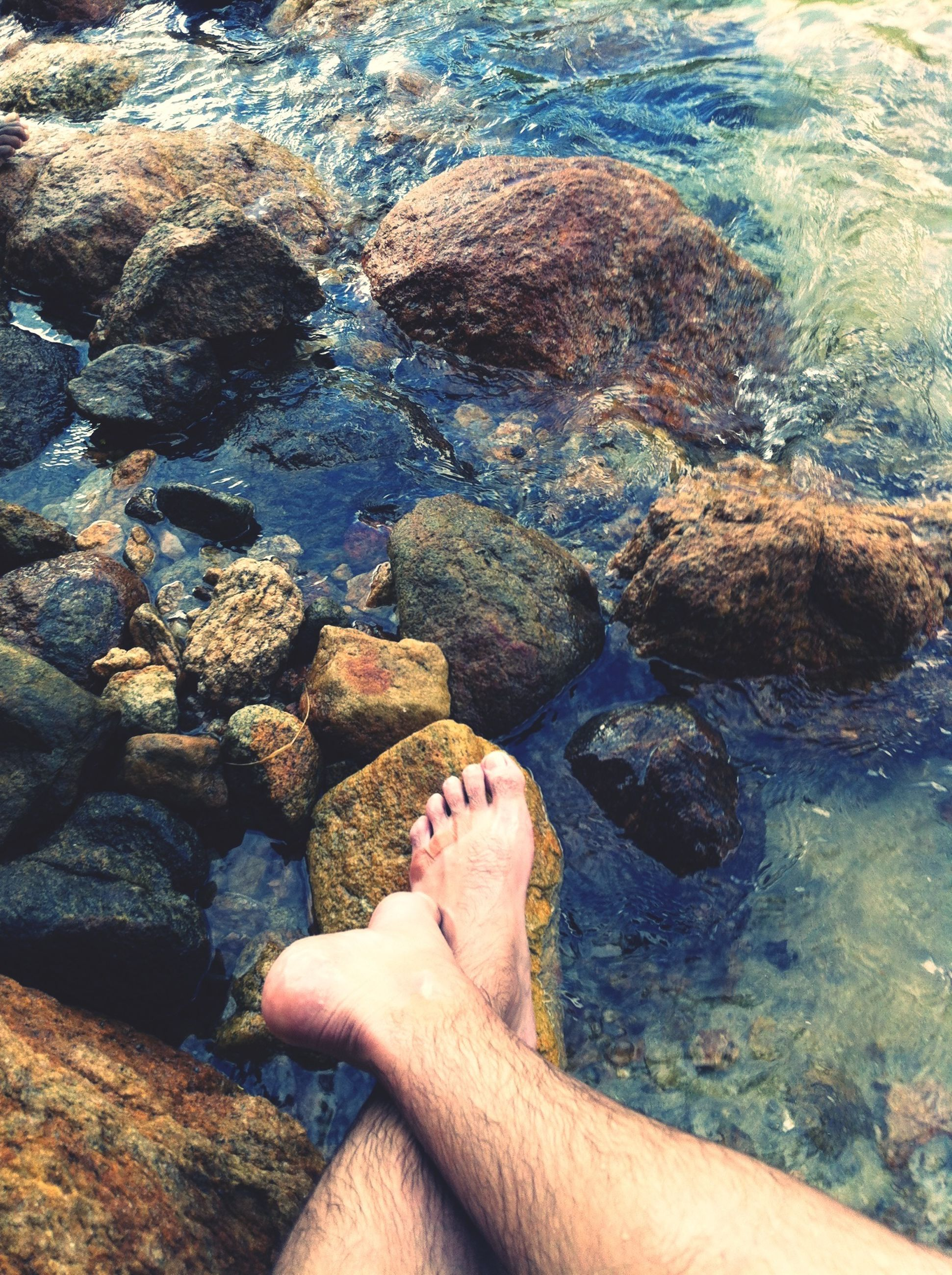 water, low section, person, personal perspective, barefoot, human foot, sea, lifestyles, high angle view, leisure activity, rock - object, relaxation, beach, resting, nature, shore