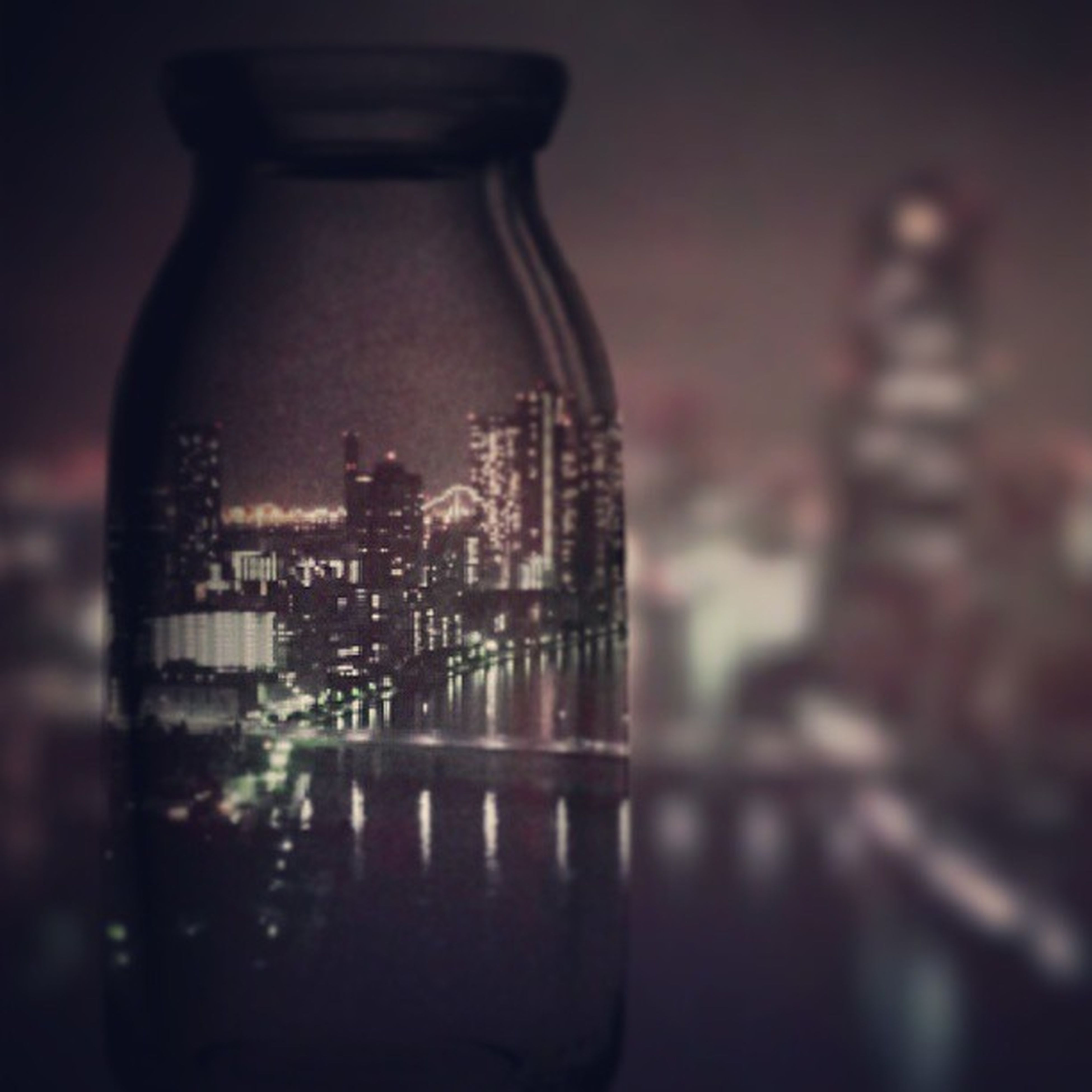 indoors, focus on foreground, illuminated, close-up, glass - material, architecture, still life, building exterior, built structure, city, no people, transparent, night, table, selective focus, modern, reflection, cityscape, metal, lighting equipment