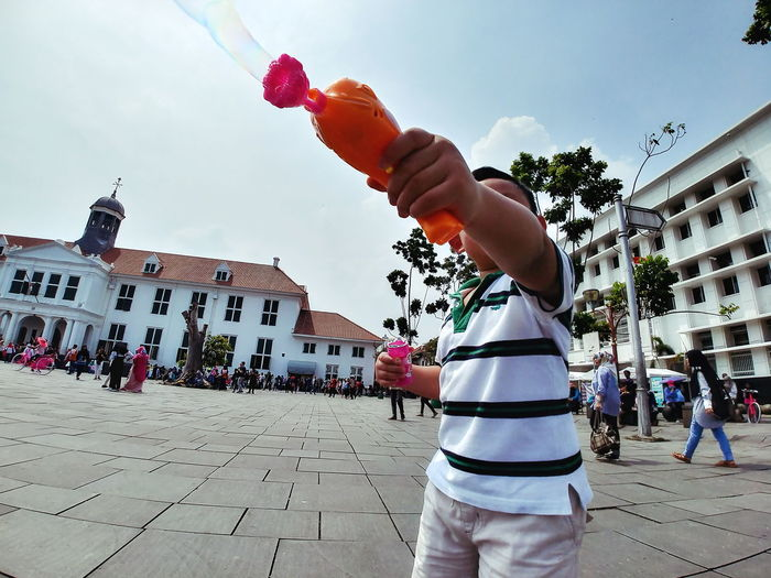 One Person People Building Exterior Outdoors Human Hand Day Men Real People Human Body Part Sky Architecture City Young Adult Crowd Historical Building Kid Building Child Large Group Of People Bubbles Bubble Gun Toy Gun Toy