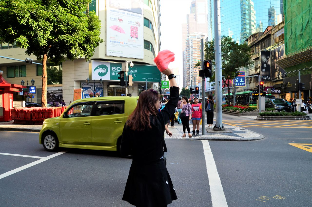 car, street, transportation, architecture, built structure, land vehicle, city, building exterior, real people, road, day, city street, city life, outdoors, walking, tree, one person, standing, women, full length, hailing, adult, people