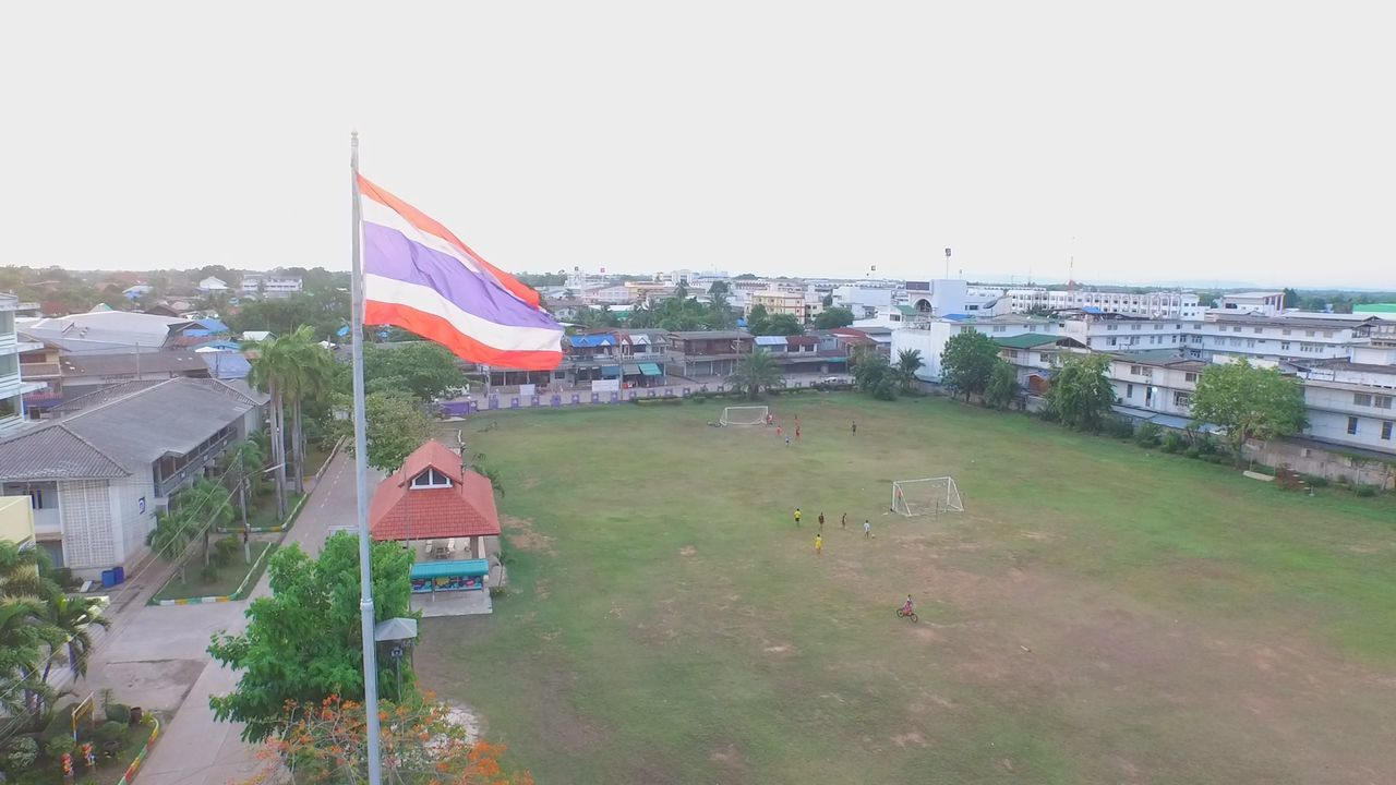 flag, architecture, patriotism, built structure, building exterior, day, outdoors, no people, city, grass, sky, clear sky, tree