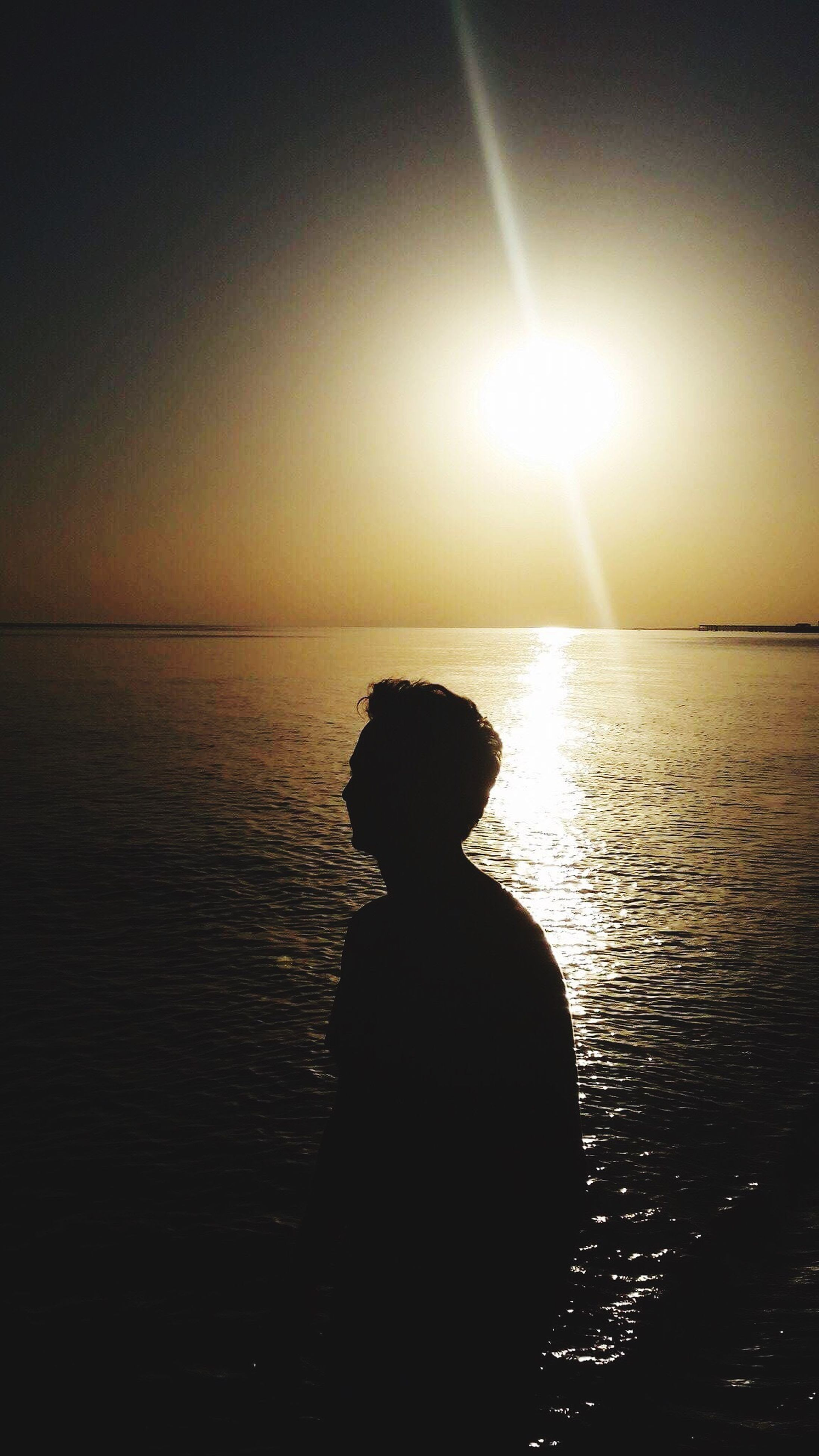sea, sunset, sun, silhouette, water, horizon over water, nature, sunbeam, scenics, one person, sunlight, tranquility, beauty in nature, tranquil scene, real people, sitting, sky, outdoors, clear sky, people