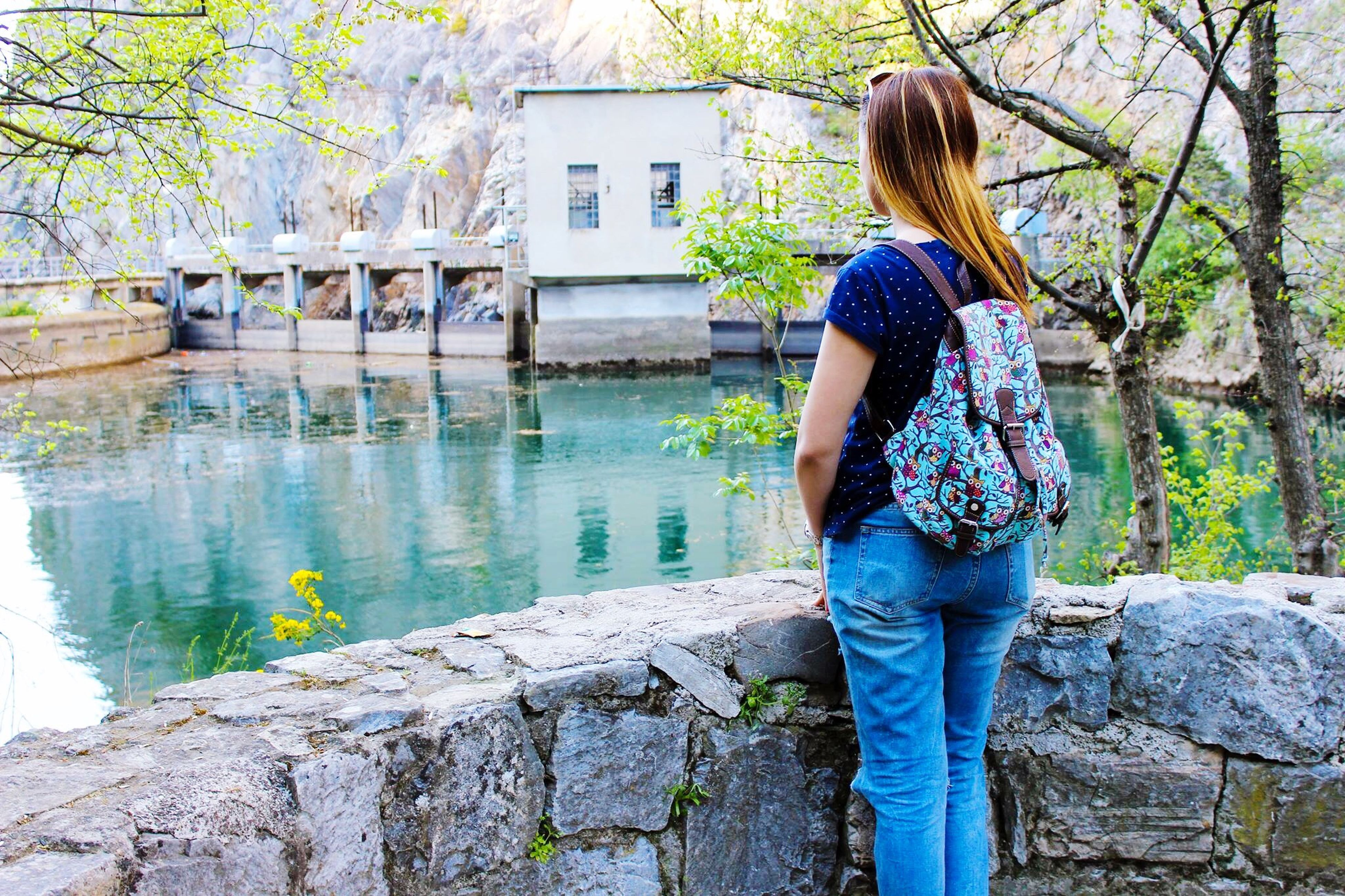 lifestyles, casual clothing, standing, full length, leisure activity, water, rear view, built structure, young adult, three quarter length, person, building exterior, tree, architecture, side view, young women, outdoors