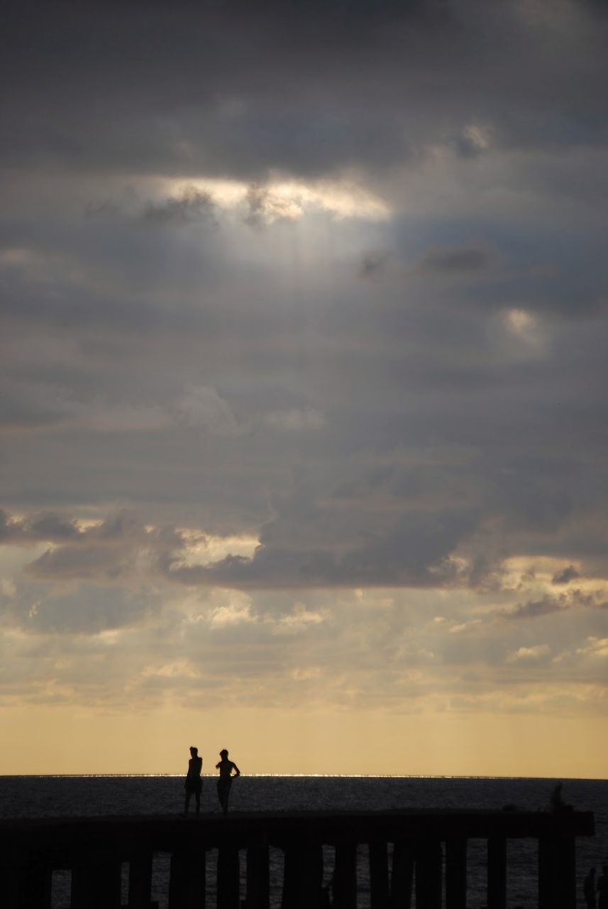 Silhouette People On Pier Over Sea Against Cloudy Sky