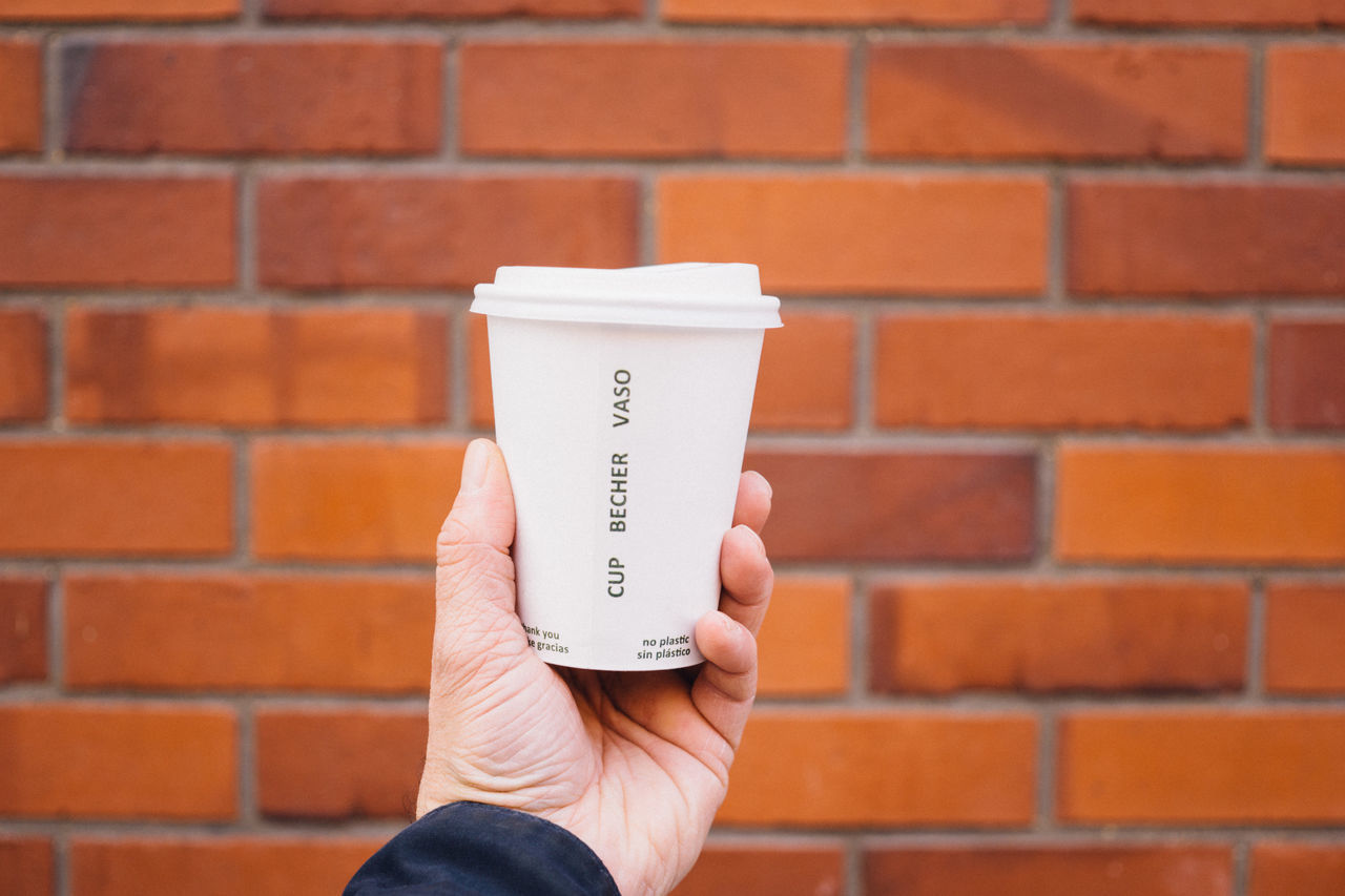 Male hand holding paper coffee cup in front of red brick wall Beverage close-up Coffee Coffee, Milk and Sugar cup hand holding Hot lid male Man paper Part of person Red to go Wall wall - building feature