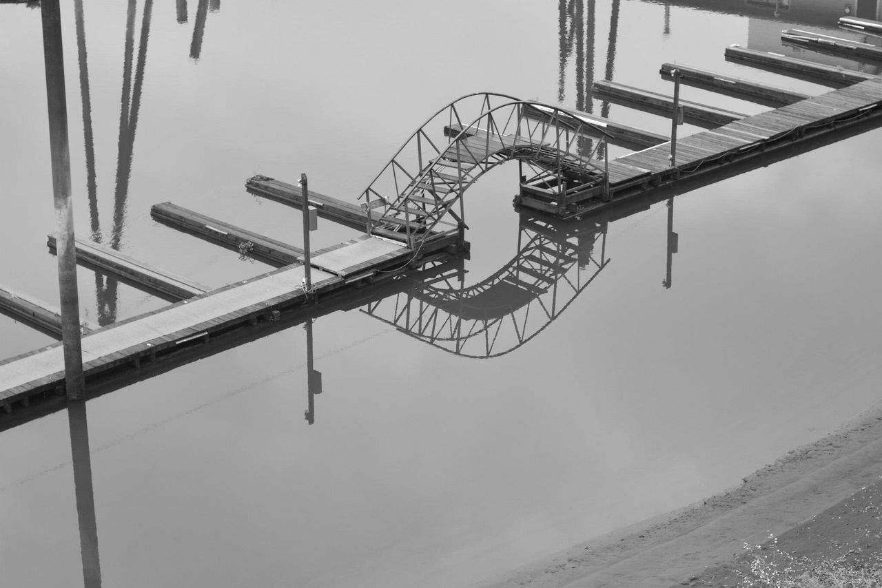 A bridge over still waters. Day Outdoors Low Angle View Built Structure No People Clear Sky Architecture Sky Water Waterfront IPhoneography Reflections Boat Dock Bridge Black & White Calm Water