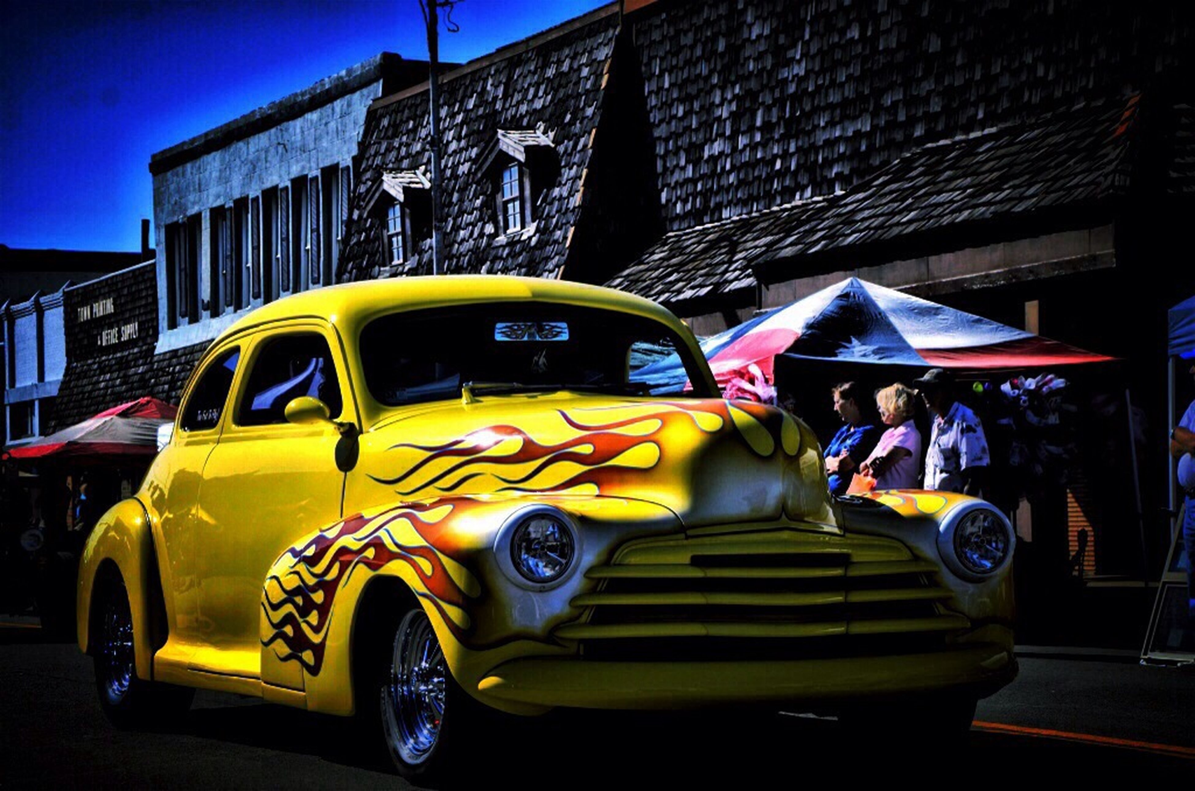 land vehicle, car, transportation, mode of transport, street, building exterior, graffiti, yellow, built structure, architecture, text, multi colored, city, stationary, western script, outdoors, road, day, blue, no people