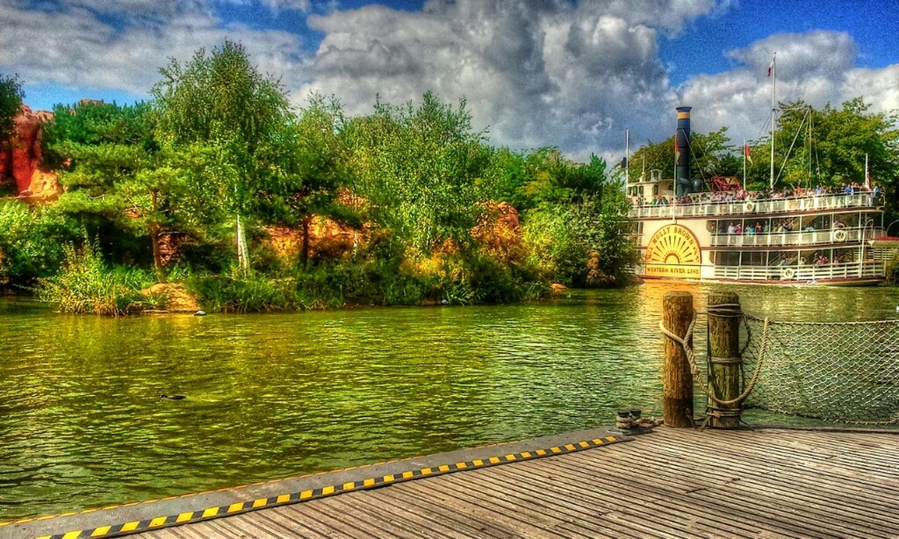 water, built structure, architecture, tree, connection, cloud, bridge - man made structure, river, sky, building exterior, engineering, day, outdoors, bridge, waterfront, walkway, cloud - sky, riverbank, calm, promenade, tranquility, pedestrian walkway, no people, tranquil scene
