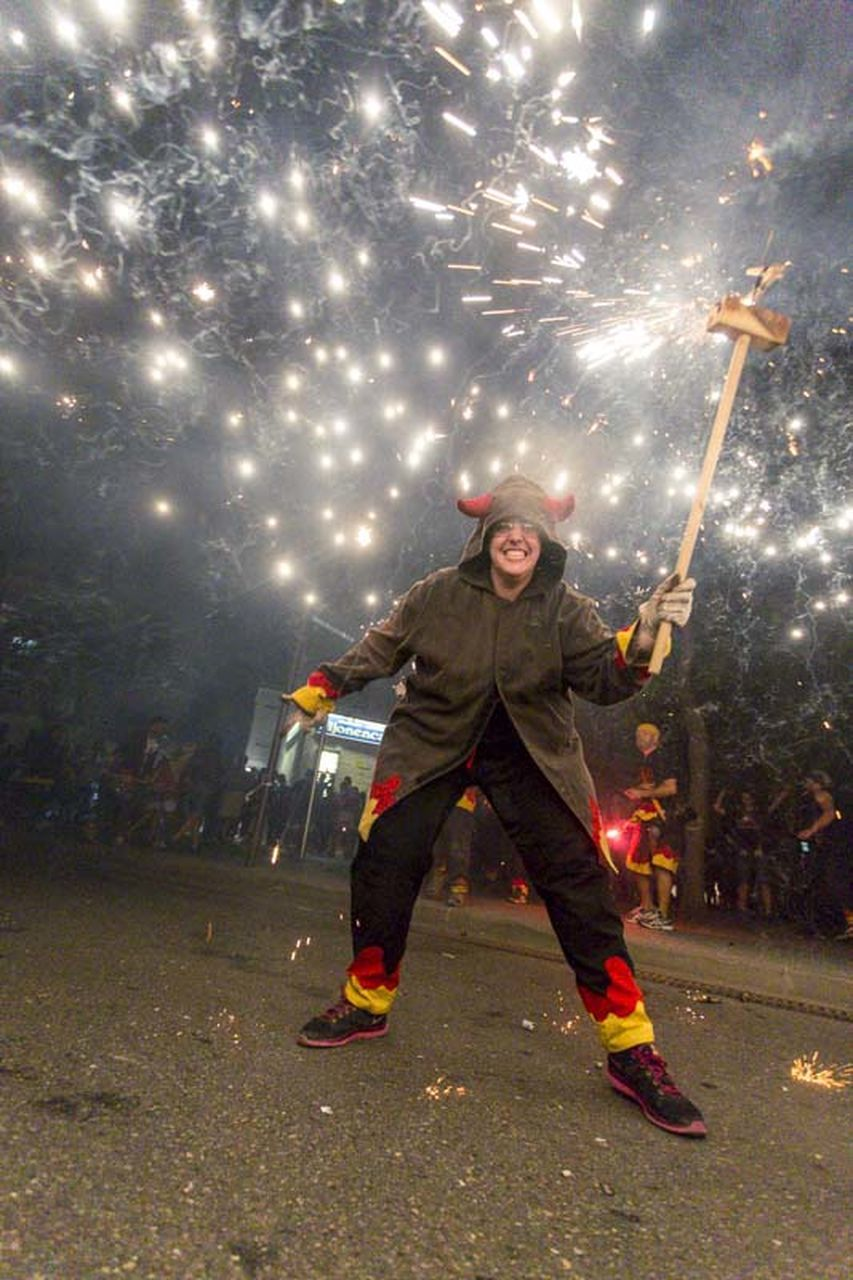 night, full length, celebration, outdoors, illuminated, front view, one person, firework - man made object, happiness, people, adult, firework, men, one man only, tree, sky, adults only, only men