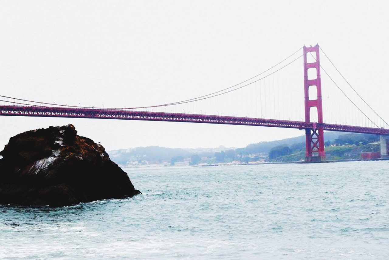 suspension bridge, bridge - man made structure, connection, sea, transportation, travel, travel destinations, nature, bridge, no people, rock - object, architecture, water, built structure, outdoors, clear sky, sky, day