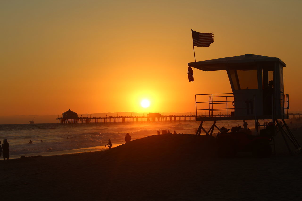 sunset, beach, sun, sea, sand, water, nature, orange color, beauty in nature, scenics, silhouette, tranquility, sky, lifeguard hut, tranquil scene, outdoors, vacations, horizon over water, real people
