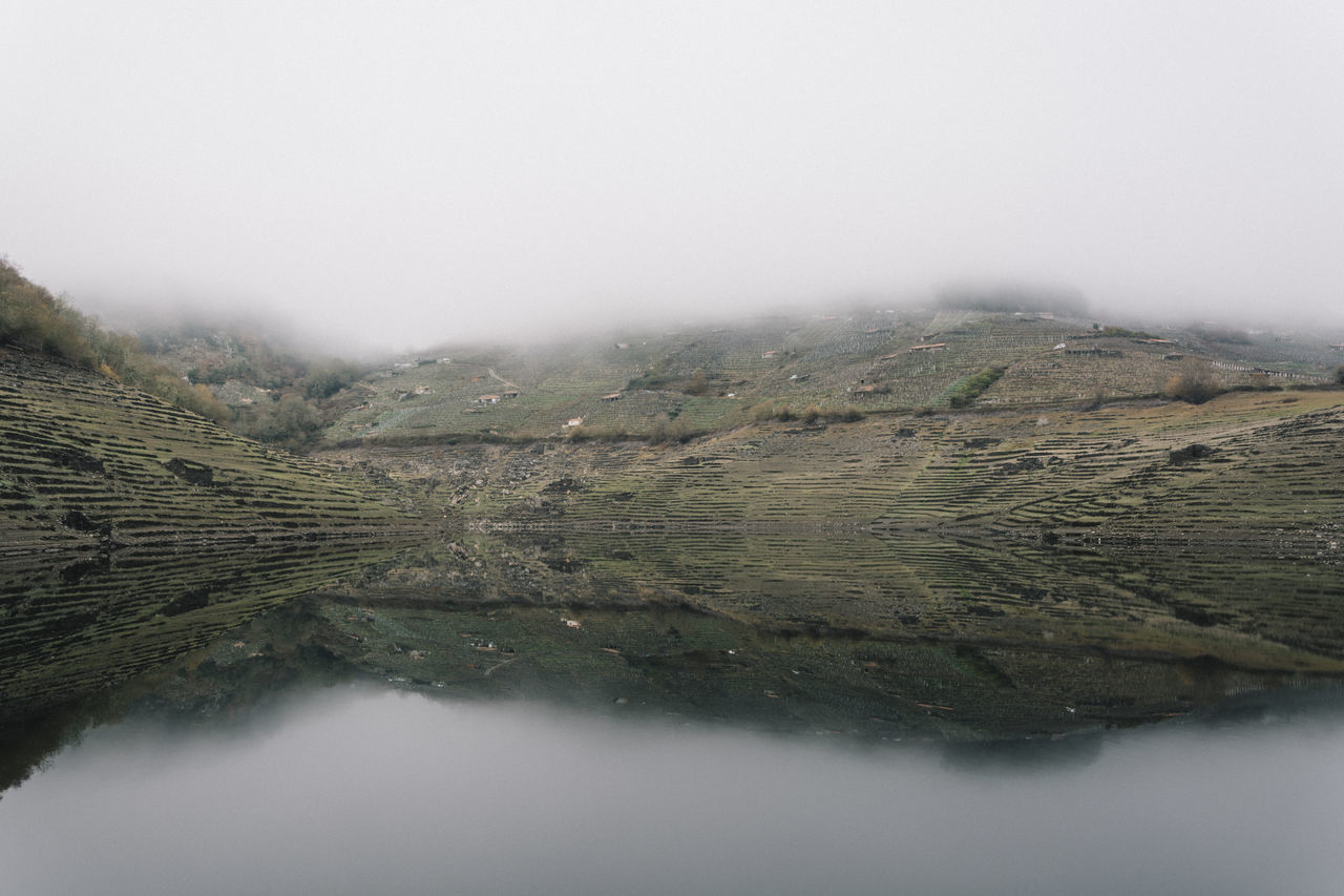 Scenic View Of Lake In Foggy Weather Against Sky