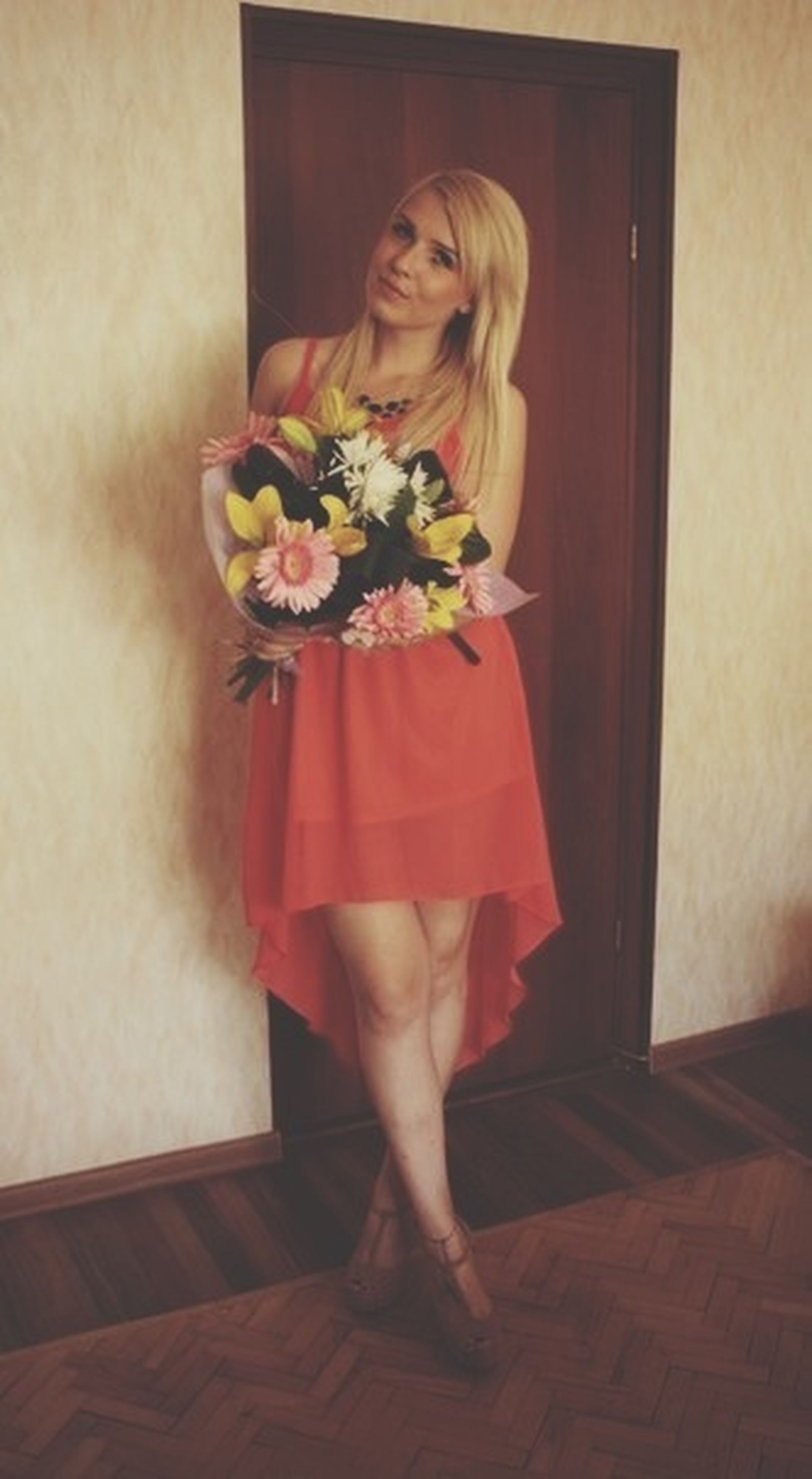 flower, indoors, red, home interior, freshness, lifestyles, holding, young women, bouquet, plant, person, front view, standing, vase, dress, wall - building feature, wood - material, table