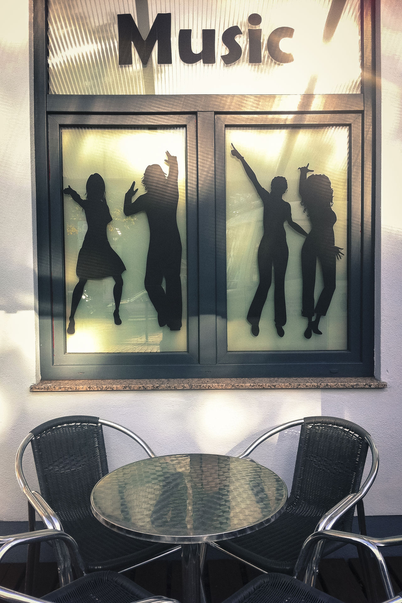 Round table with chairs outside music bar 'music' Bar Chairs Dancing Entertainment Outdoors Reflections Shadows Sun Table Text Vertical