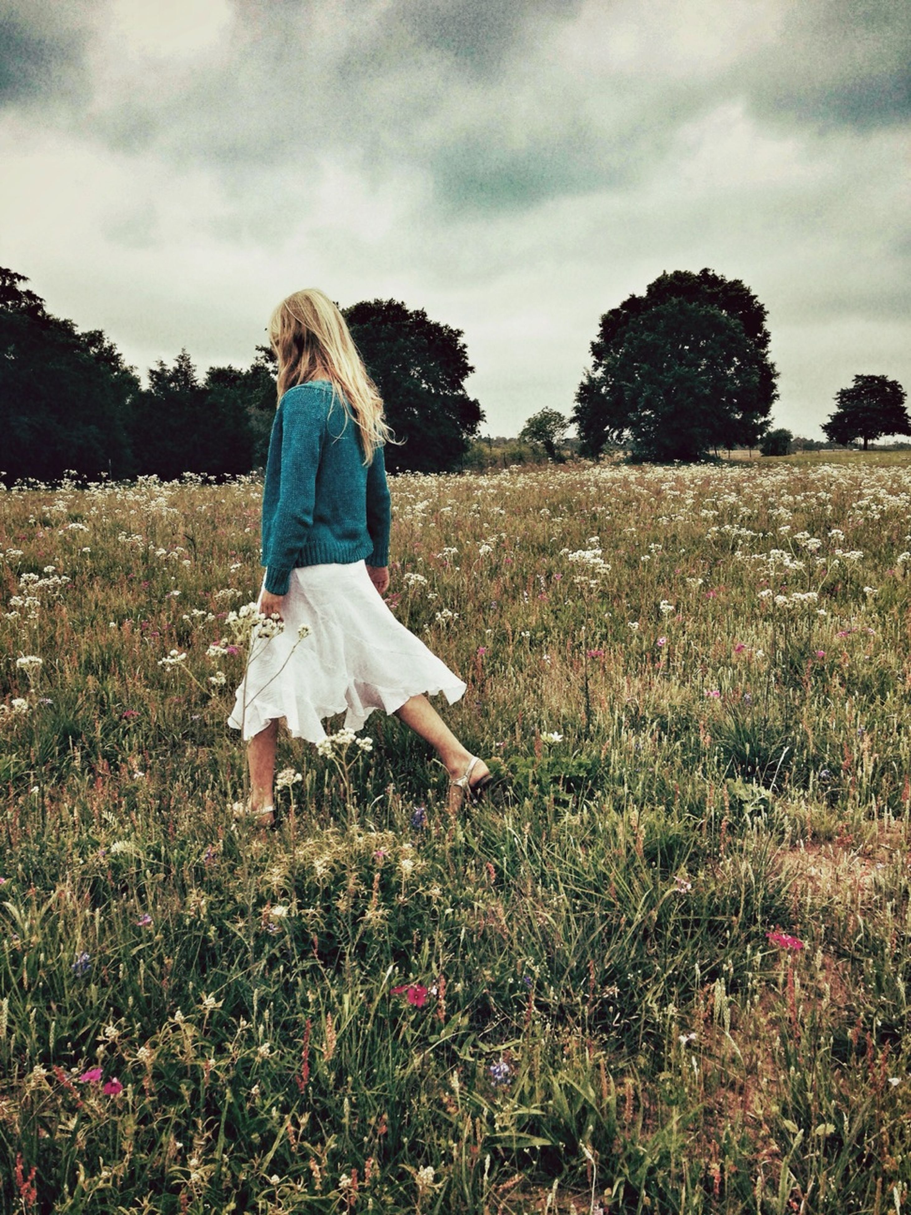 field, sky, lifestyles, leisure activity, landscape, grass, full length, cloud - sky, casual clothing, growth, rear view, tranquil scene, nature, tranquility, standing, beauty in nature, plant, tree