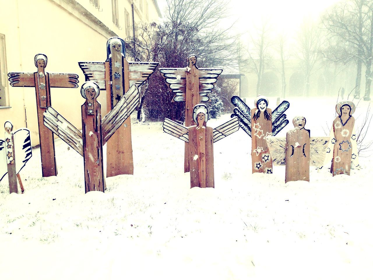 Wooden Statues On Snow Covered Field By Building