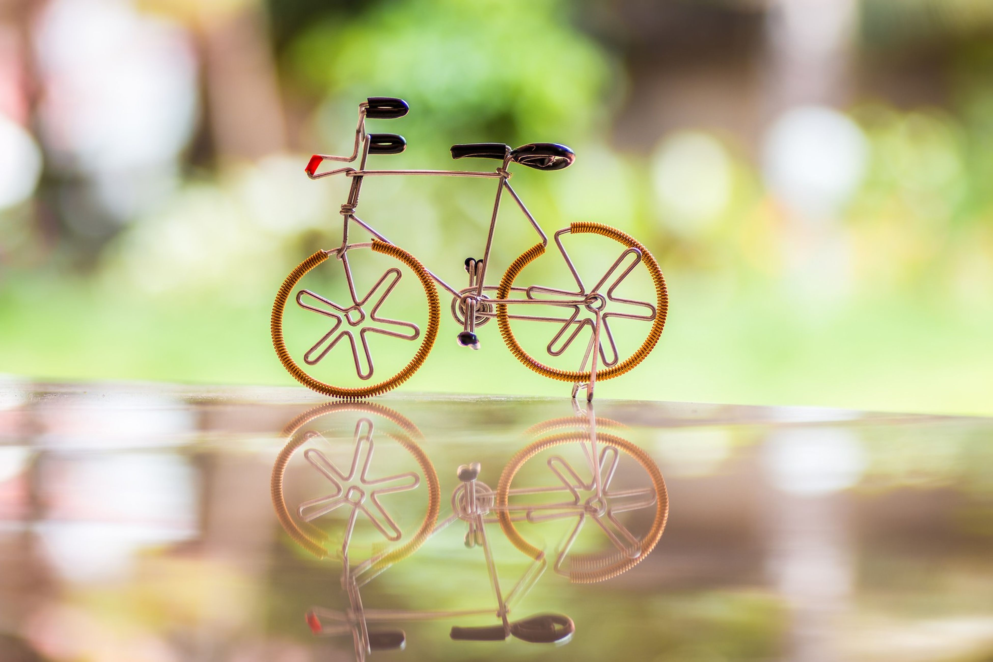 focus on foreground, close-up, metal, selective focus, circle, no people, metallic, bicycle, day, outdoors, railing, hanging, still life, pattern, fence, reflection, built structure, protection, man made object