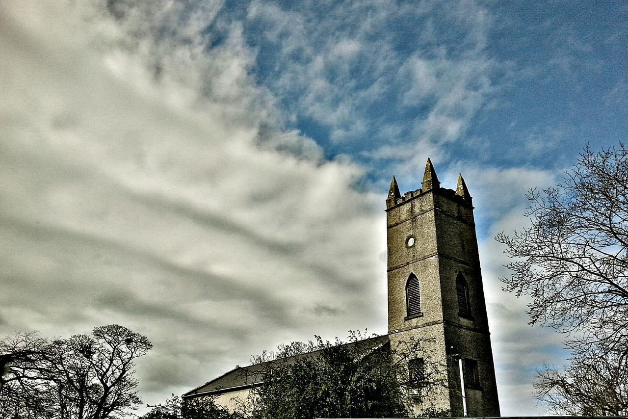 tower, history, sky, architecture, cloud - sky, religion, low angle view, day, place of worship, clock tower, tree, spirituality, built structure, travel destinations, building exterior, bell tower, outdoors, no people