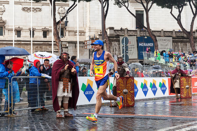 Rome, Italy - March 22, 2015: Giorgio Calcaterra, the finish line at 21 Rome Marathon. Athlete Atletic Calcaterra City Life Competition Day Finish Line  Gladiator Italy Marathon Outdoors Rain Roma Rome Runners Running Street Street Running Water
