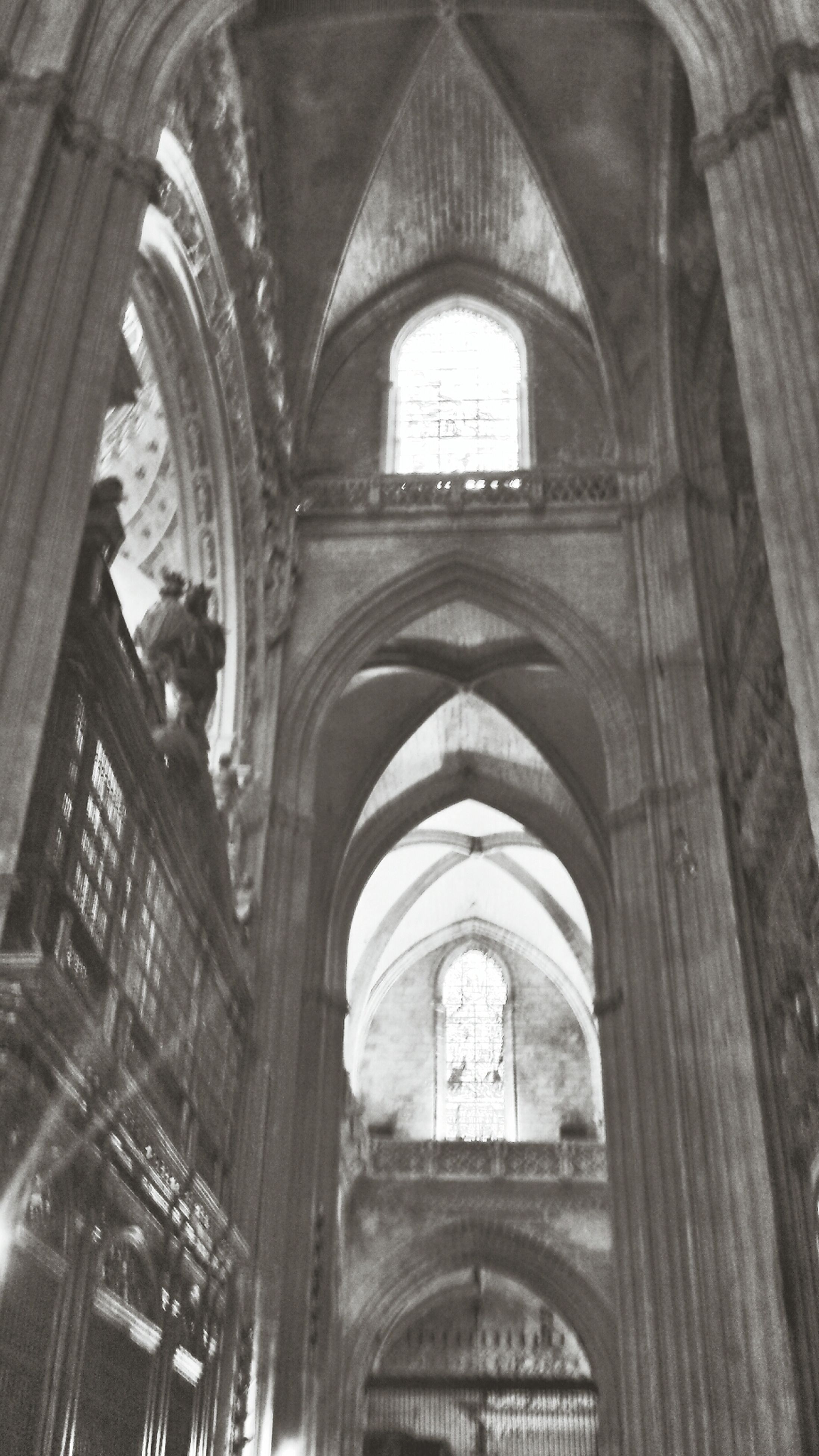 arch, indoors, architecture, church, place of worship, religion, built structure, spirituality, low angle view, cathedral, history, interior, window, old, ceiling, architectural column, no people, architectural feature
