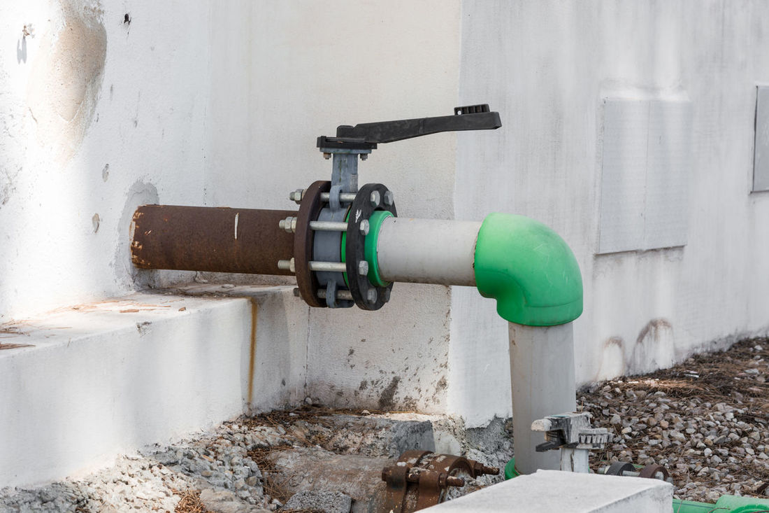 Gray old valve and green water pipe. Industrial water valve or control valve. Architecture Building Exterior Built Structure Close-up Day No People Outdoors Pipe - Tube Tap Wall - Building Feature Water