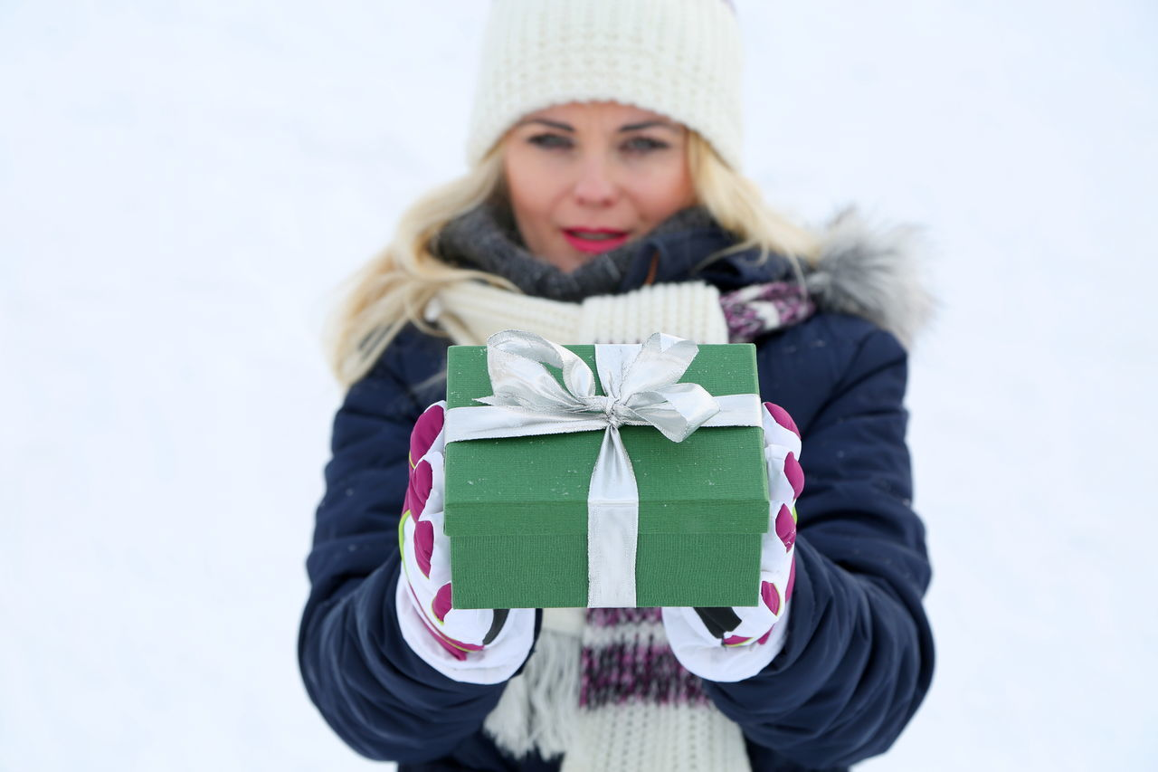 Adult Celebration Christmas Christmas Present Cold Temperature Gift Giving Glove Holding Knit Hat Looking At Camera Love One Woman Only One Young Woman Only Outdoors Portrait Snow Surprise Valentine's Day  Warm Clothing Winter Wrapped Young Adult Uniqueness