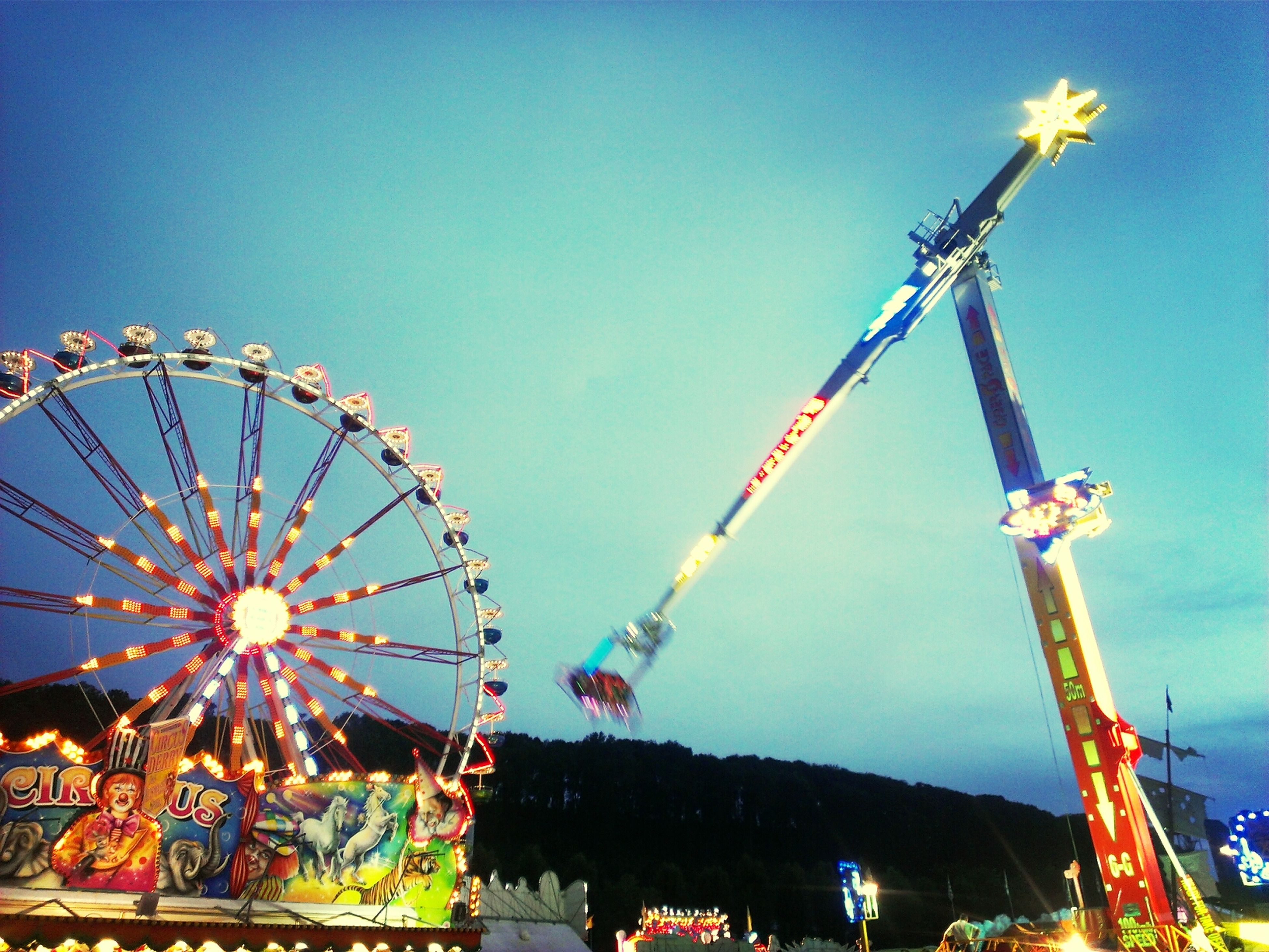 amusement park, amusement park ride, arts culture and entertainment, illuminated, low angle view, ferris wheel, clear sky, night, copy space, fun, sky, blue, carousel, chain swing ride, enjoyment, built structure, outdoors, lighting equipment, dusk, traveling carnival