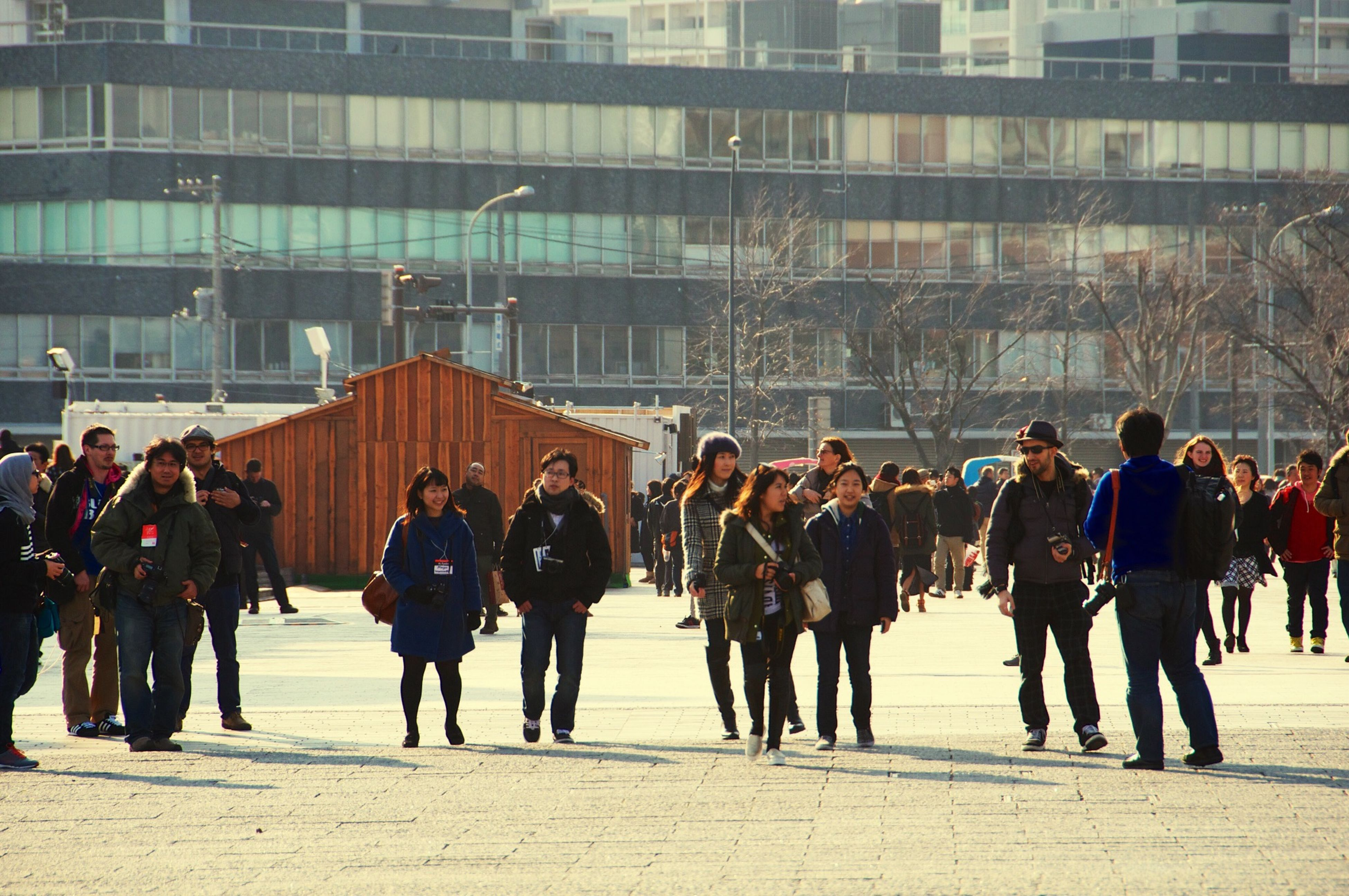 large group of people, architecture, built structure, building exterior, person, men, lifestyles, walking, city life, leisure activity, city, street, mixed age range, full length, day, outdoors, sunlight, building, travel