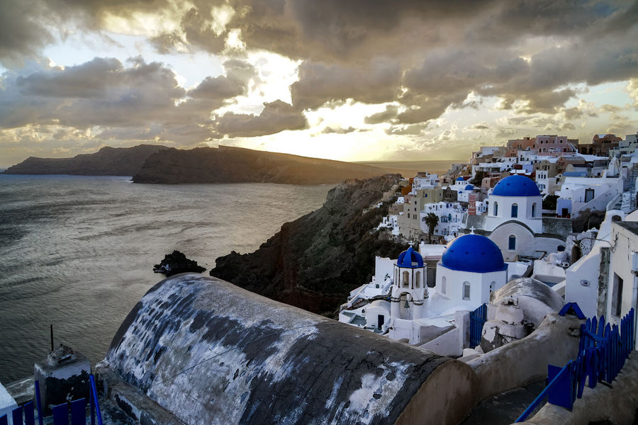 Sunset with the three blue domes of Oia. Greece Santorini Oia Oia Santorini Europe Hellas Blue Dome Sunset Sky Ocean Cliff Outdoors Travel Beach Sea Cloud - Sky Sand Beauty In Nature People Day