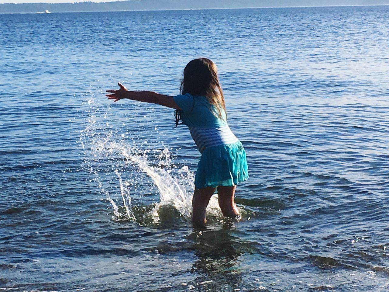 sea, water, one person, rippled, real people, rear view, nature, day, outdoors, standing, horizon over water, full length, leisure activity, ankle deep in water, lifestyles, women, childhood, beauty in nature, wave, sky, adult, people