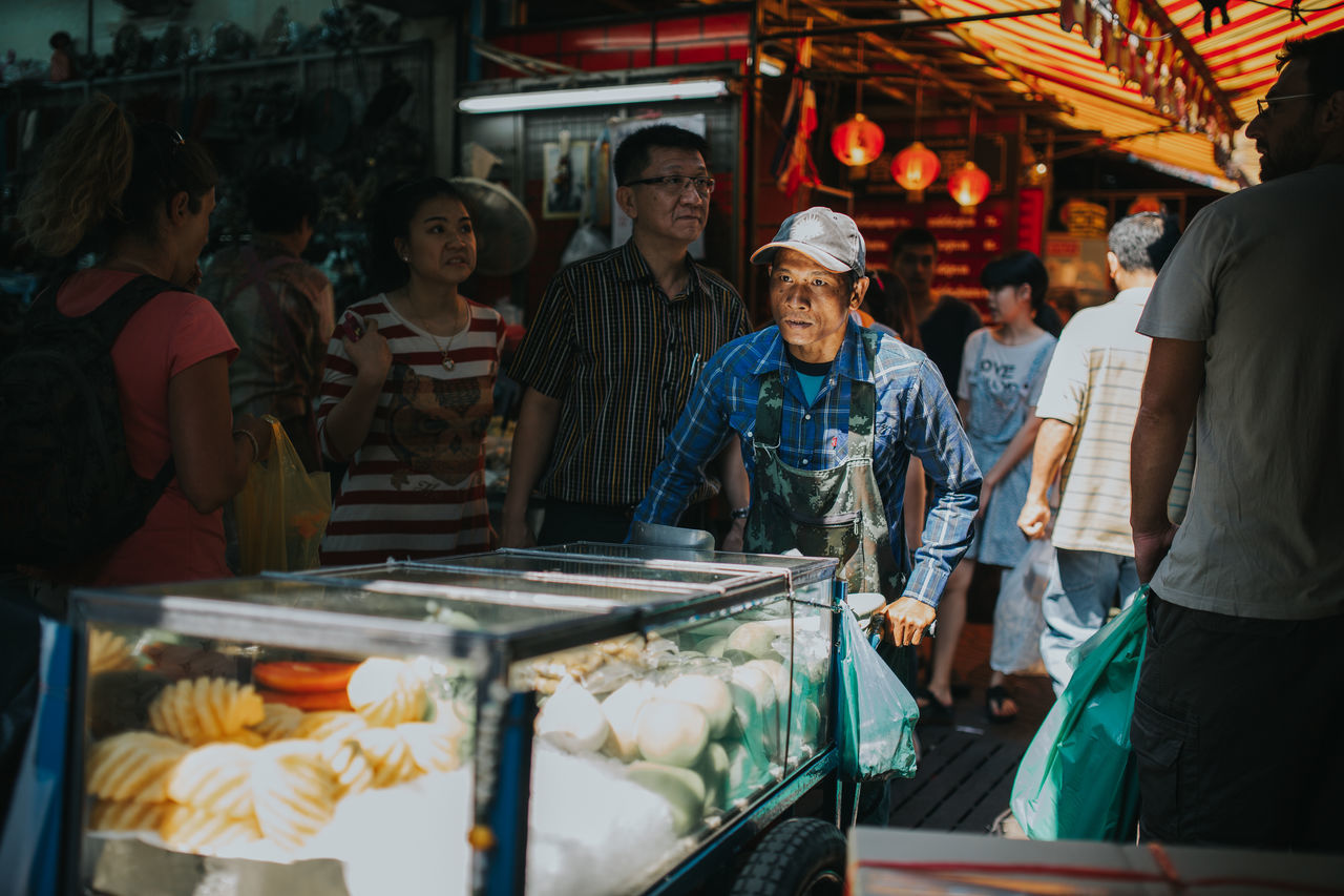 real people, food and drink, market, men, standing, food, retail, women, night, outdoors, young adult, adult, people