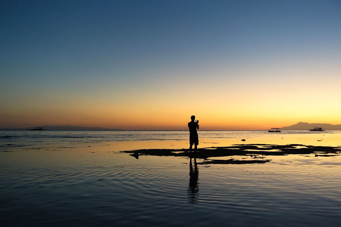 Silhouette of man taking sunset pictures on a calm island beach Background Beach Sunrise Beach Sunset Centered Digital Nomad Filipino Freedom Grounded Inspirational Island Living Island Sunset Island View  Islands It's More Fun In The Philippines Philipines Philippine Islands Photographer Silhouette Solo Travel Solo Traveler Solo Traveller The Philippines Vagabond Wanderer Zen