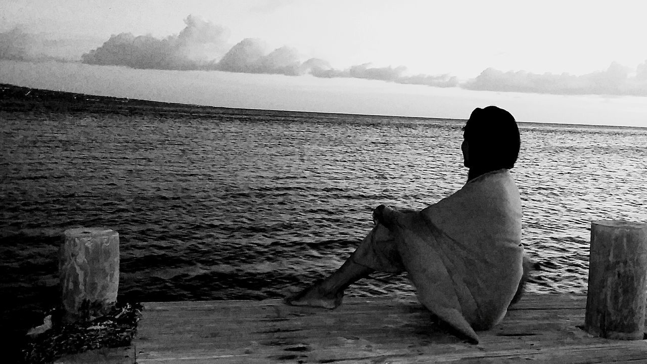 sea, water, rear view, one person, sitting, horizon over water, tranquil scene, nature, outdoors, women, sky, scenics, looking at view, tranquility, beauty in nature, relaxation, day, full length, real people, adult, people