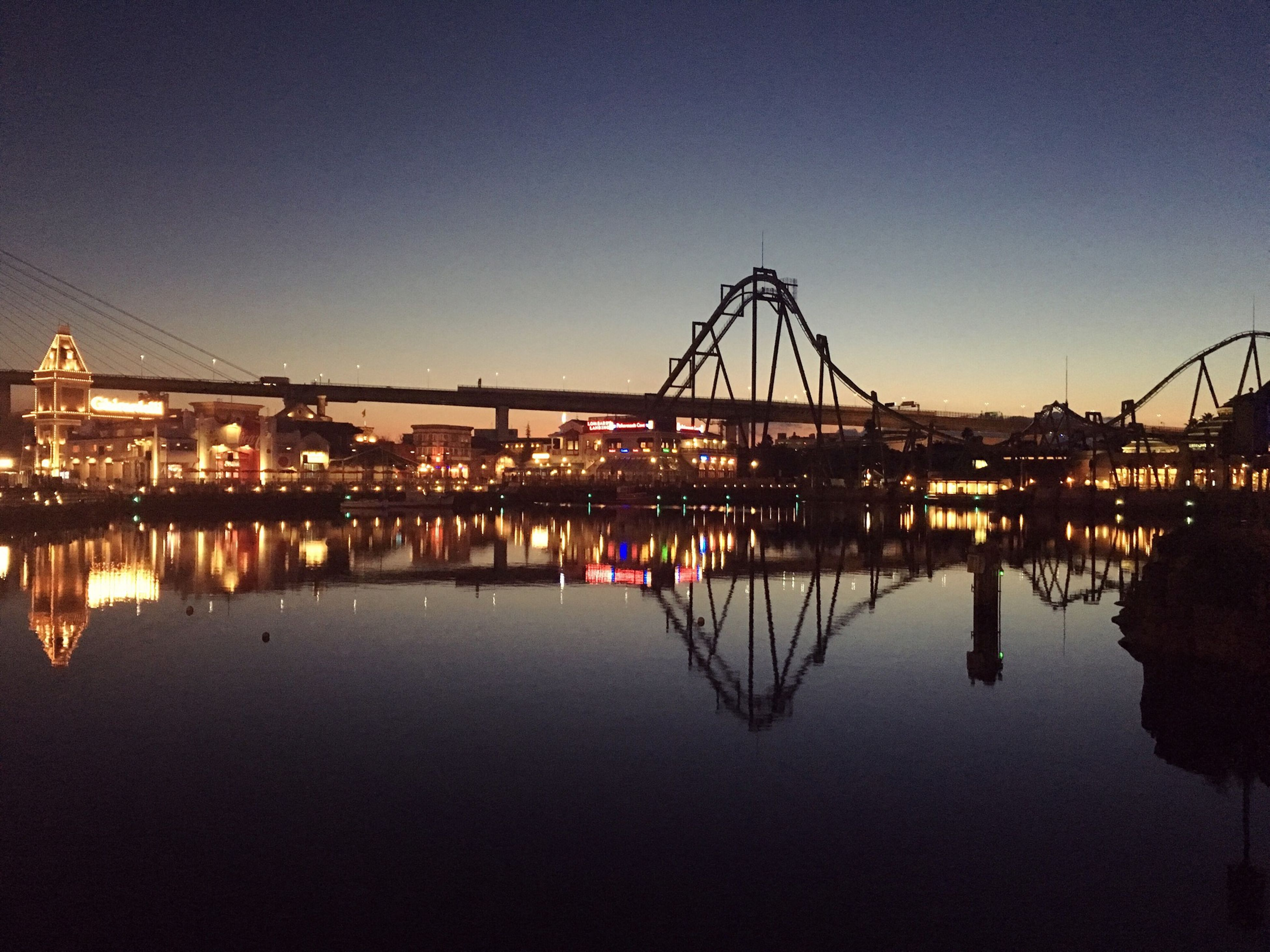 water, reflection, architecture, built structure, waterfront, clear sky, illuminated, connection, river, copy space, standing water, dusk, bridge - man made structure, building exterior, night, blue, sky, tranquility, transportation, outdoors