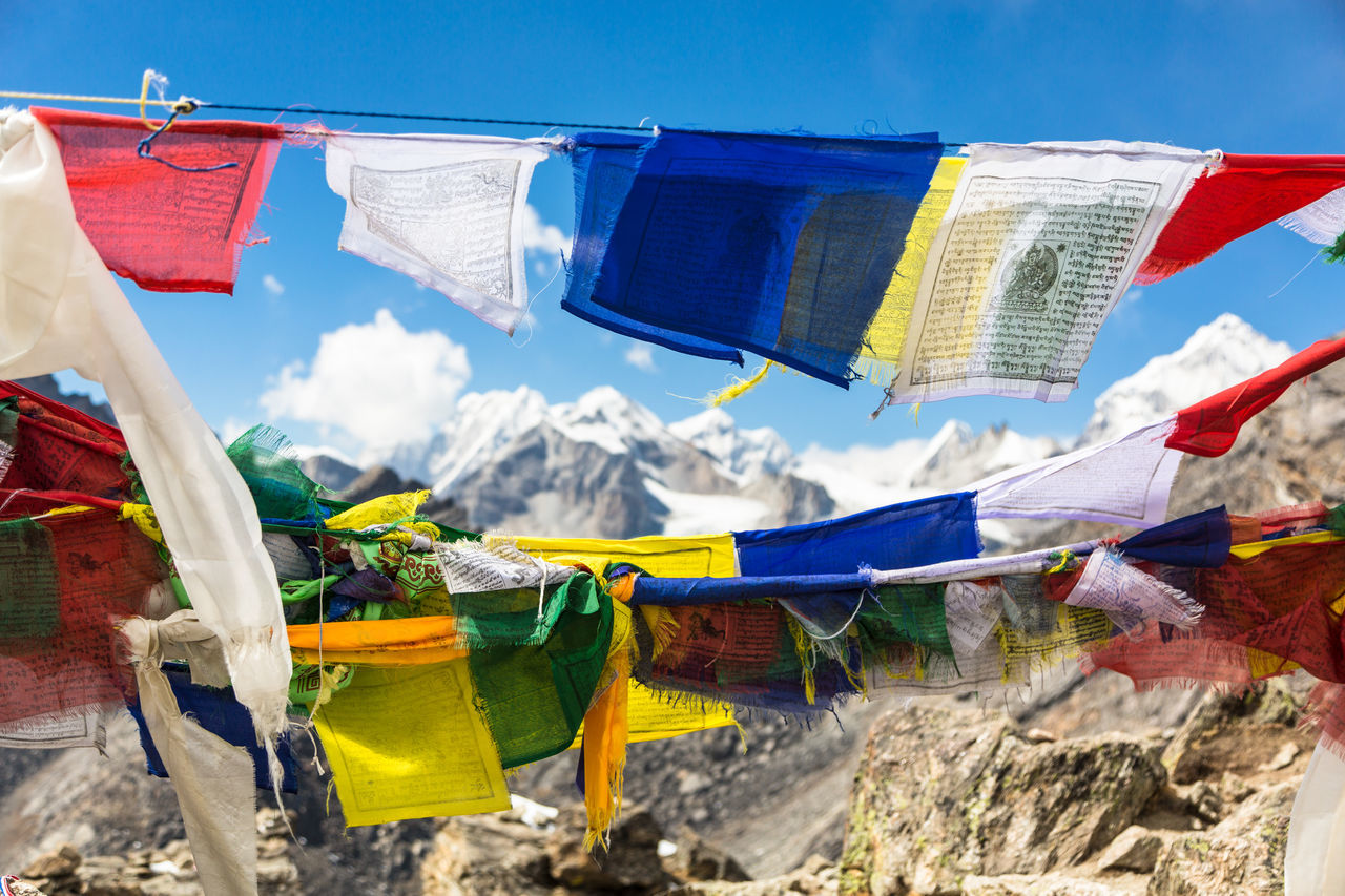Tibetan Buddhist prayer flags on the top of Gokyo Ri in the Himalayas mountain range in Nepal Beauty In Nature Blue Sky Buddhism Day Gokyo Gokyo Peak Hiking Himalayas Landscape Mountain Multi Colored Nature Nature Nepal Outdoors Peace Prayer Flags  Sky Snow Capped Mountains Summit Tranquil Scene Travel Trekking